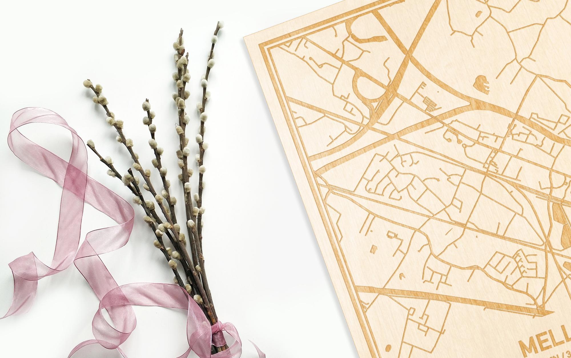 Hier ligt de houten plattegrond Melle naast een bloemetje als gepersonaliseerd cadeau voor haar.