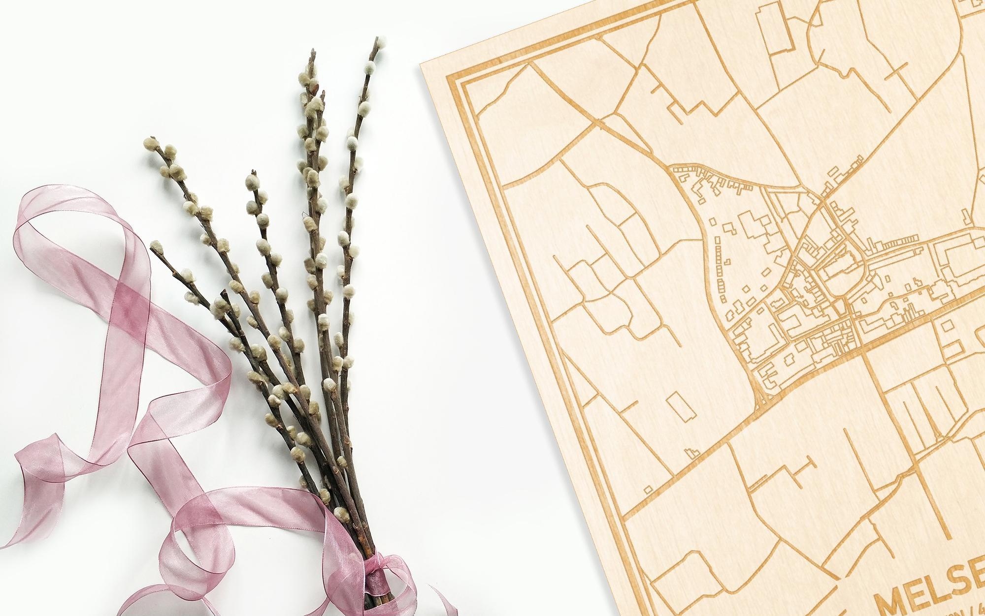Hier ligt de houten plattegrond Melsele naast een bloemetje als gepersonaliseerd cadeau voor haar.