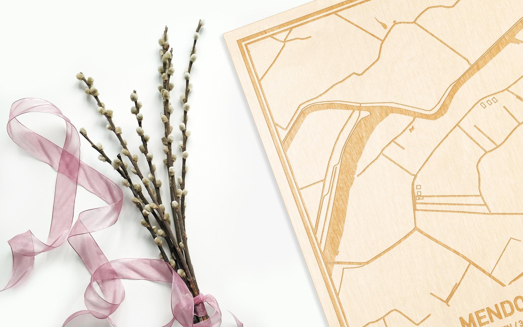 Hier ligt de houten plattegrond Mendonk naast een bloemetje als gepersonaliseerd cadeau voor haar.
