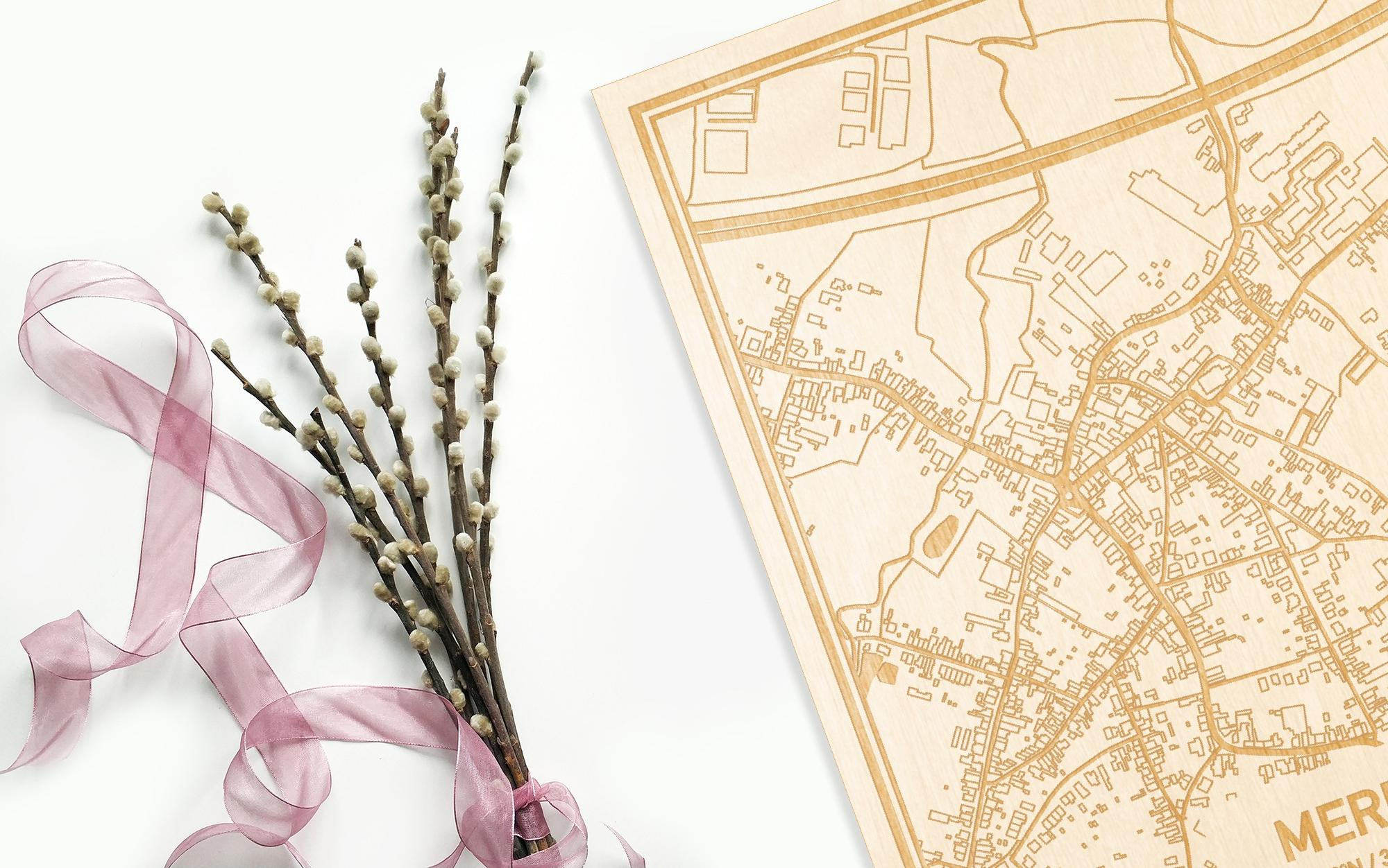 Hier ligt de houten plattegrond Mere naast een bloemetje als gepersonaliseerd cadeau voor haar.
