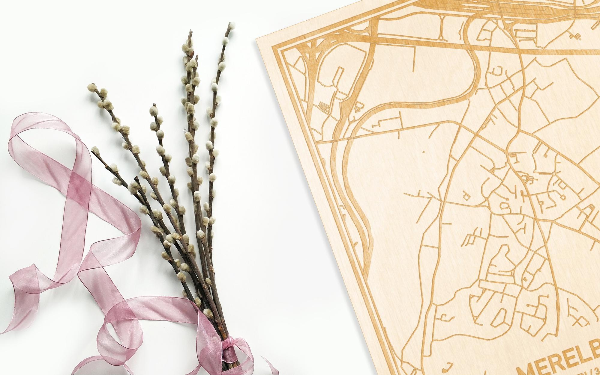 Hier ligt de houten plattegrond Merelbeke naast een bloemetje als gepersonaliseerd cadeau voor haar.