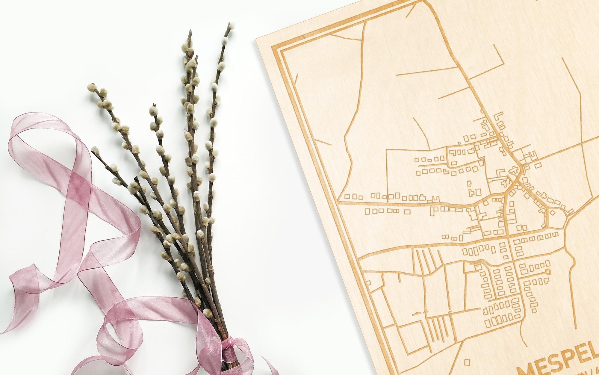 Hier ligt de houten plattegrond Mespelare naast een bloemetje als gepersonaliseerd cadeau voor haar.