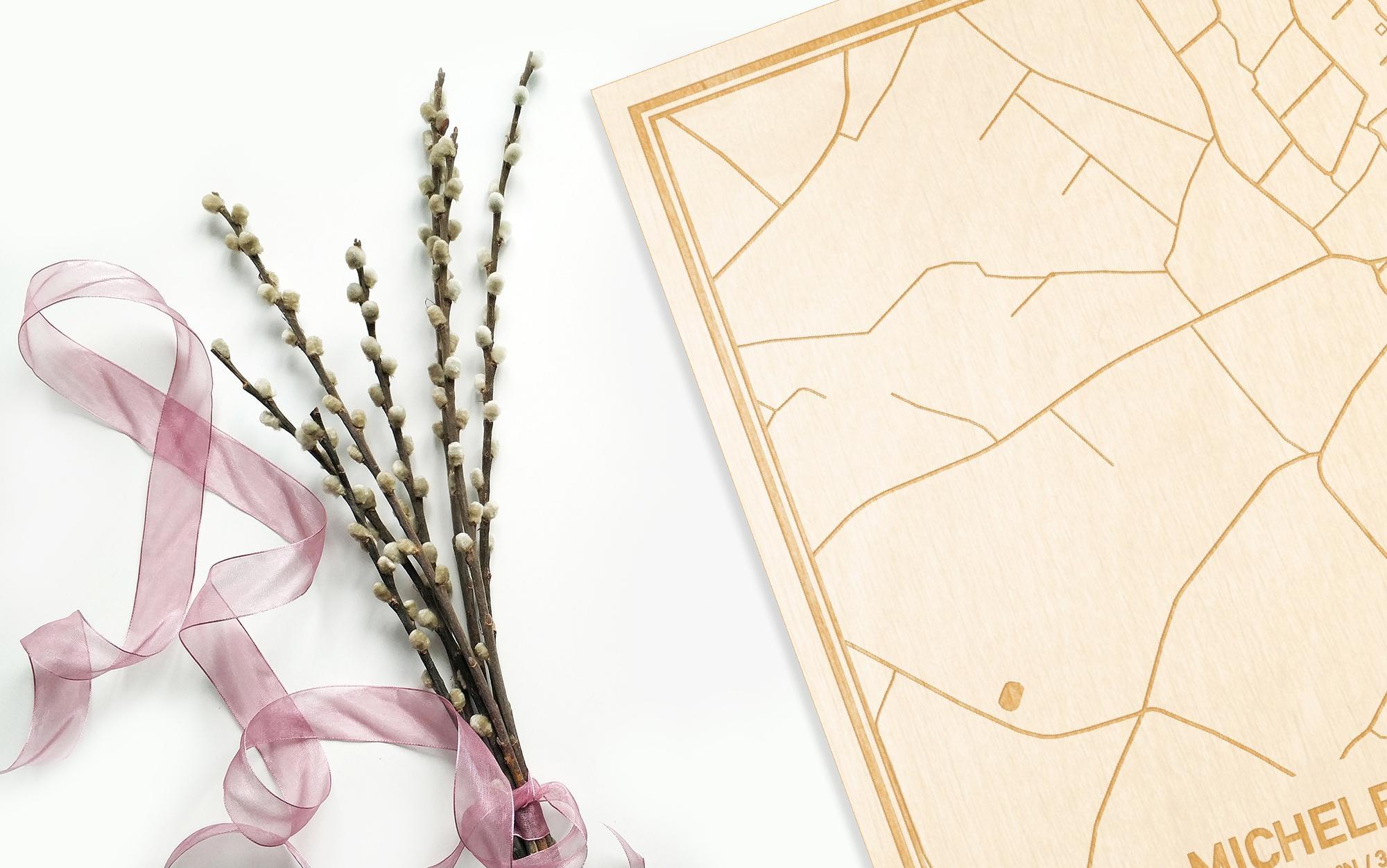 Hier ligt de houten plattegrond Michelbeke naast een bloemetje als gepersonaliseerd cadeau voor haar.