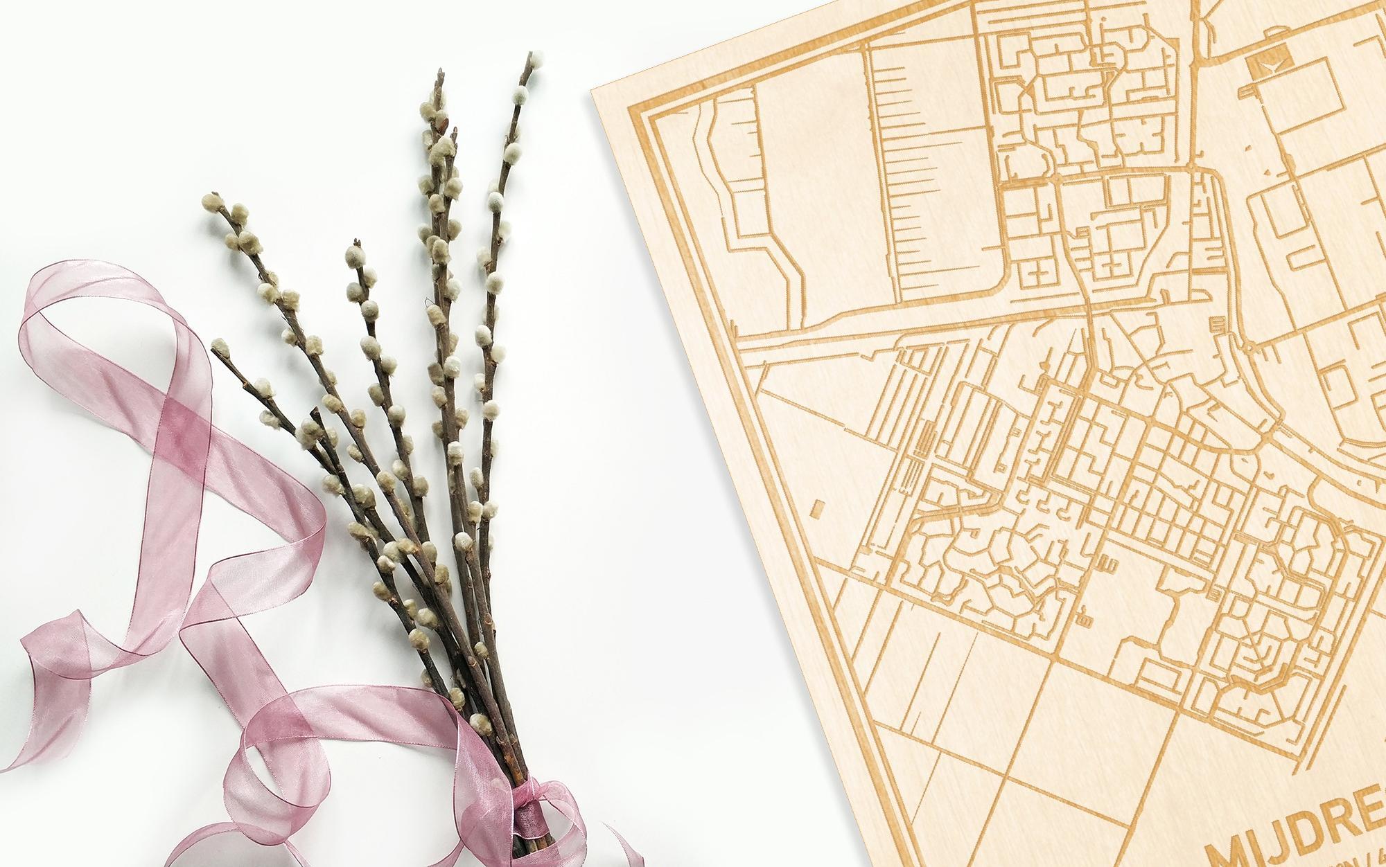 Hier ligt de houten plattegrond Mijdrecht naast een bloemetje als gepersonaliseerd cadeau voor haar.