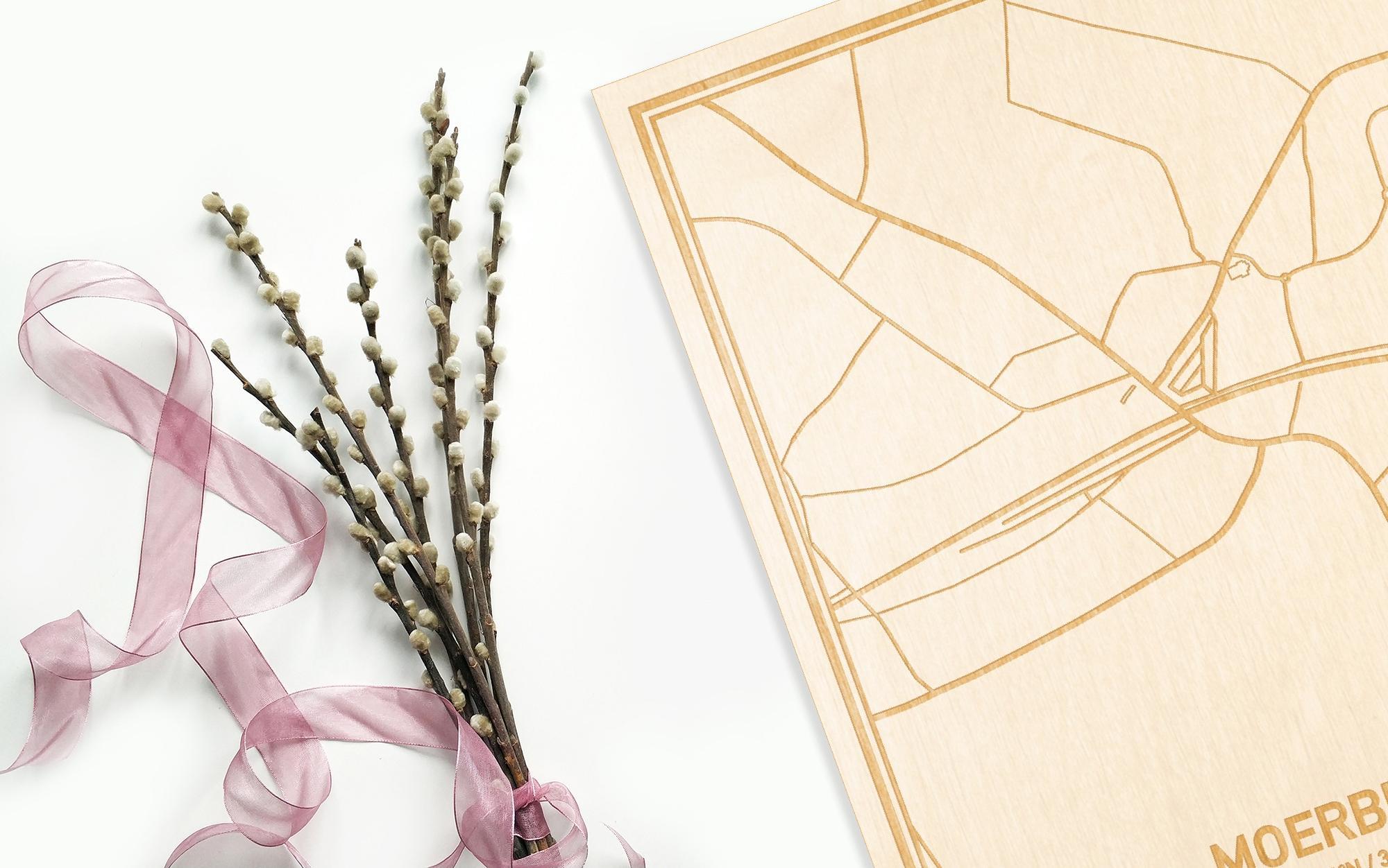 Hier ligt de houten plattegrond Moerbeke naast een bloemetje als gepersonaliseerd cadeau voor haar.
