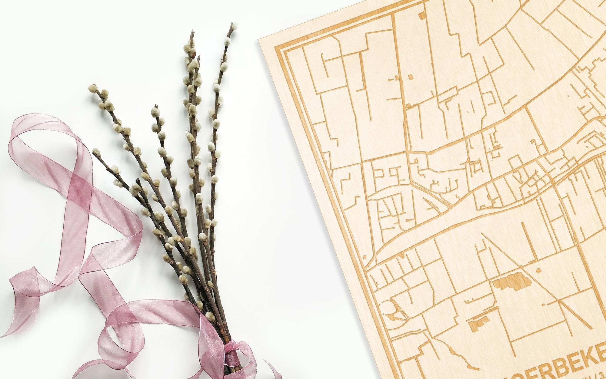 Hier ligt de houten plattegrond Moerbeke-Waas naast een bloemetje als gepersonaliseerd cadeau voor haar.