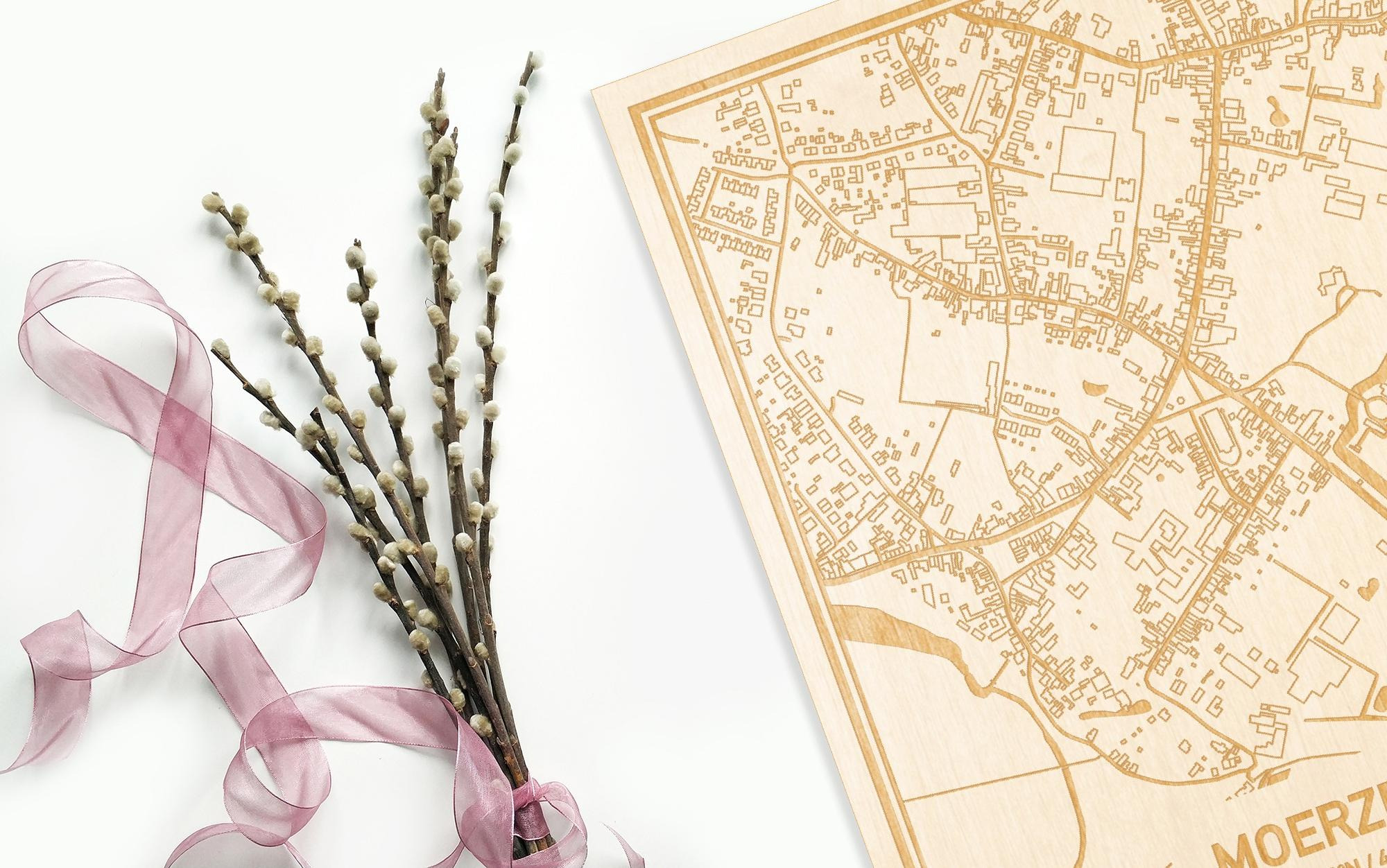 Hier ligt de houten plattegrond Moerzeke naast een bloemetje als gepersonaliseerd cadeau voor haar.