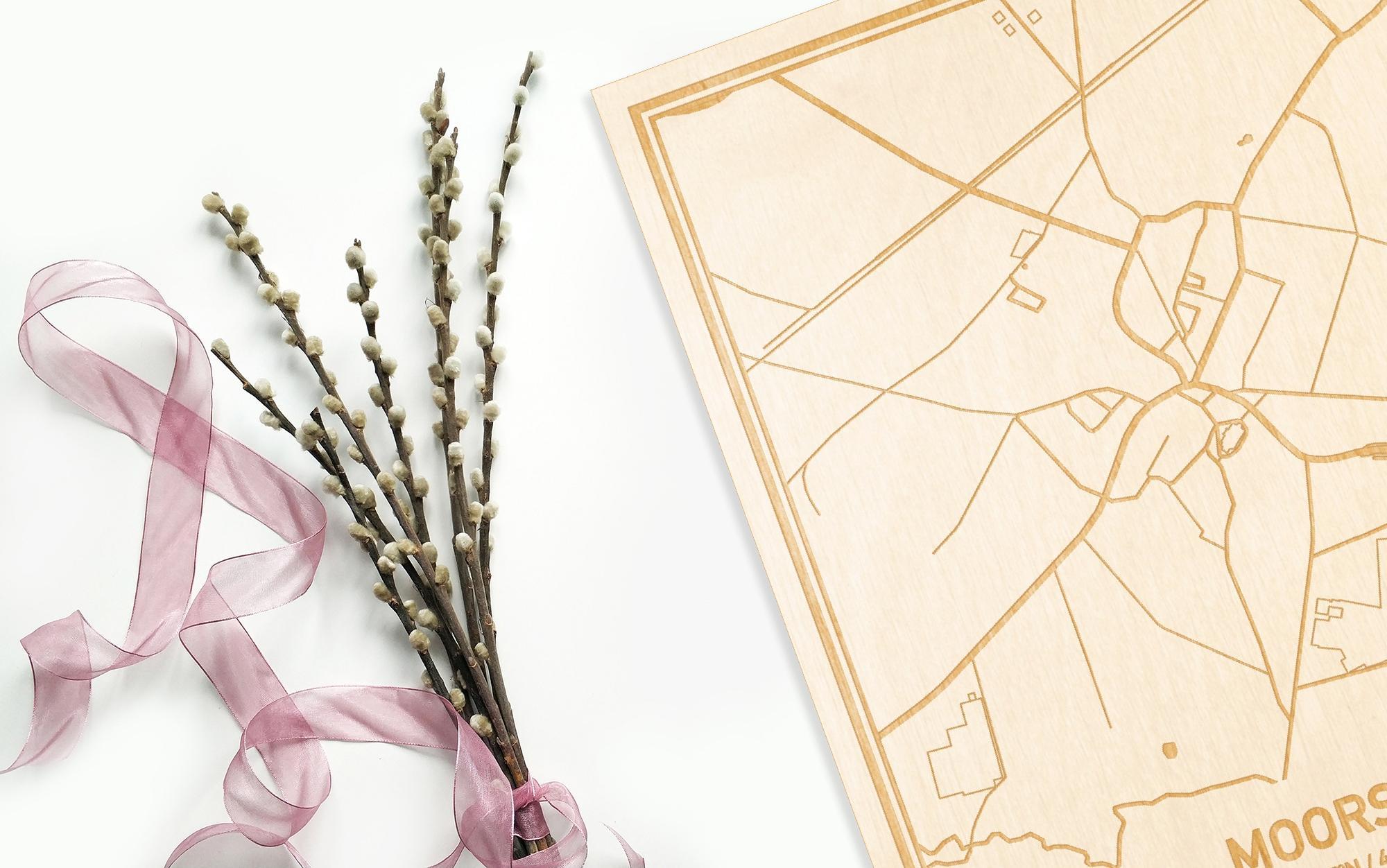 Hier ligt de houten plattegrond Moorsel naast een bloemetje als gepersonaliseerd cadeau voor haar.