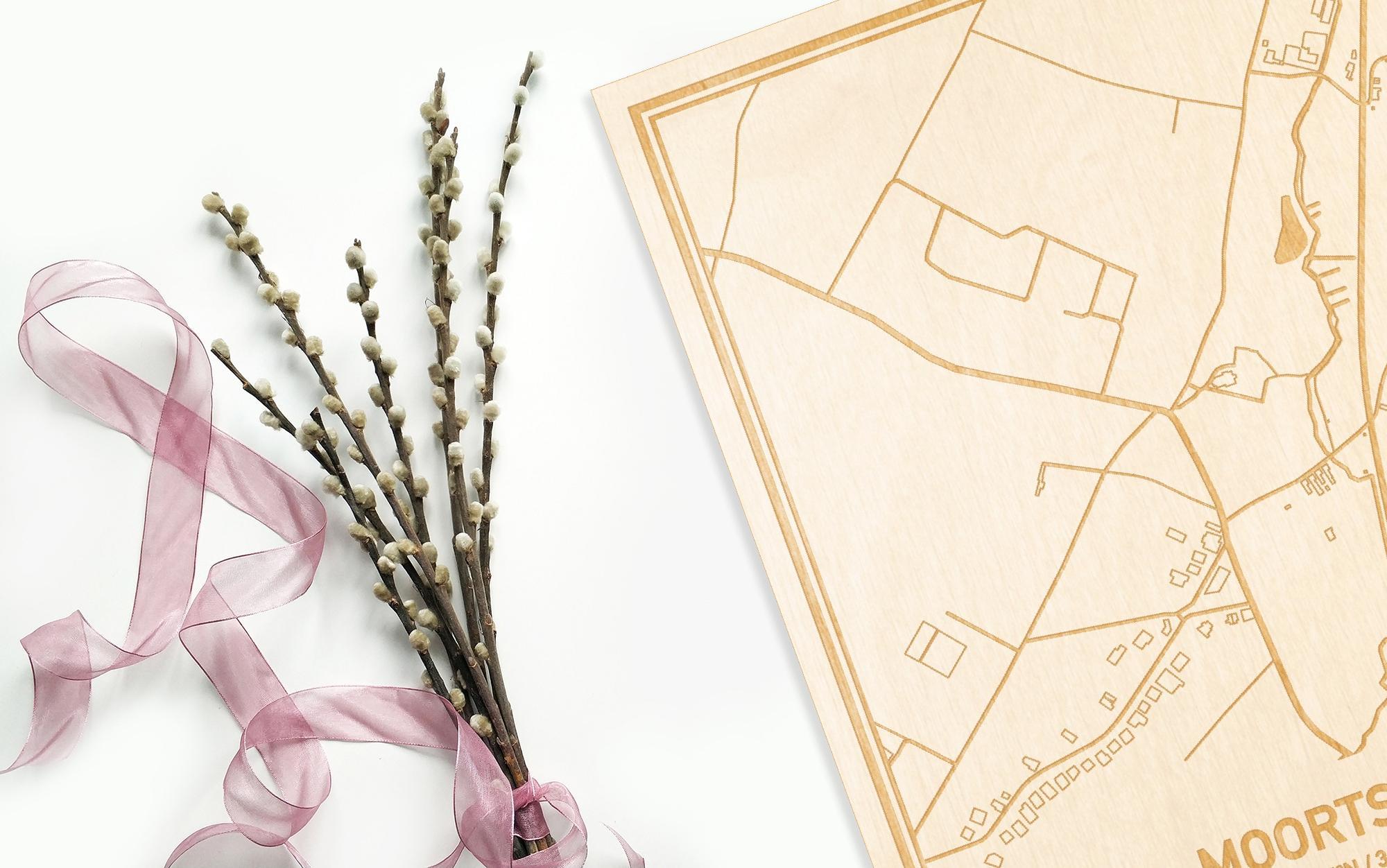 Hier ligt de houten plattegrond Moortsele naast een bloemetje als gepersonaliseerd cadeau voor haar.