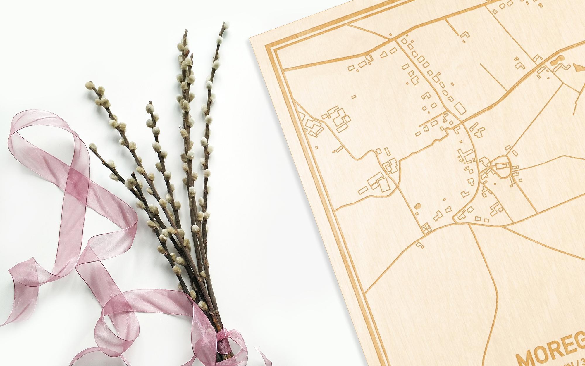 Hier ligt de houten plattegrond Moregem naast een bloemetje als gepersonaliseerd cadeau voor haar.