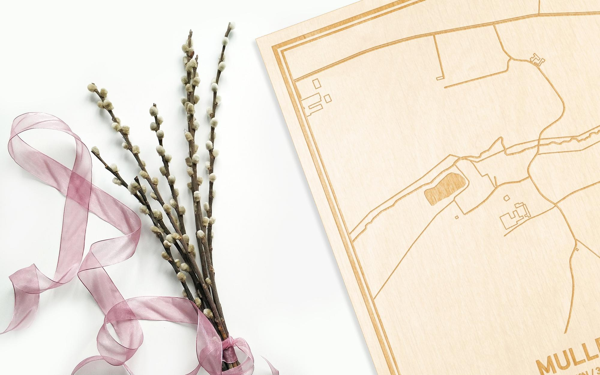 Hier ligt de houten plattegrond Mullem naast een bloemetje als gepersonaliseerd cadeau voor haar.