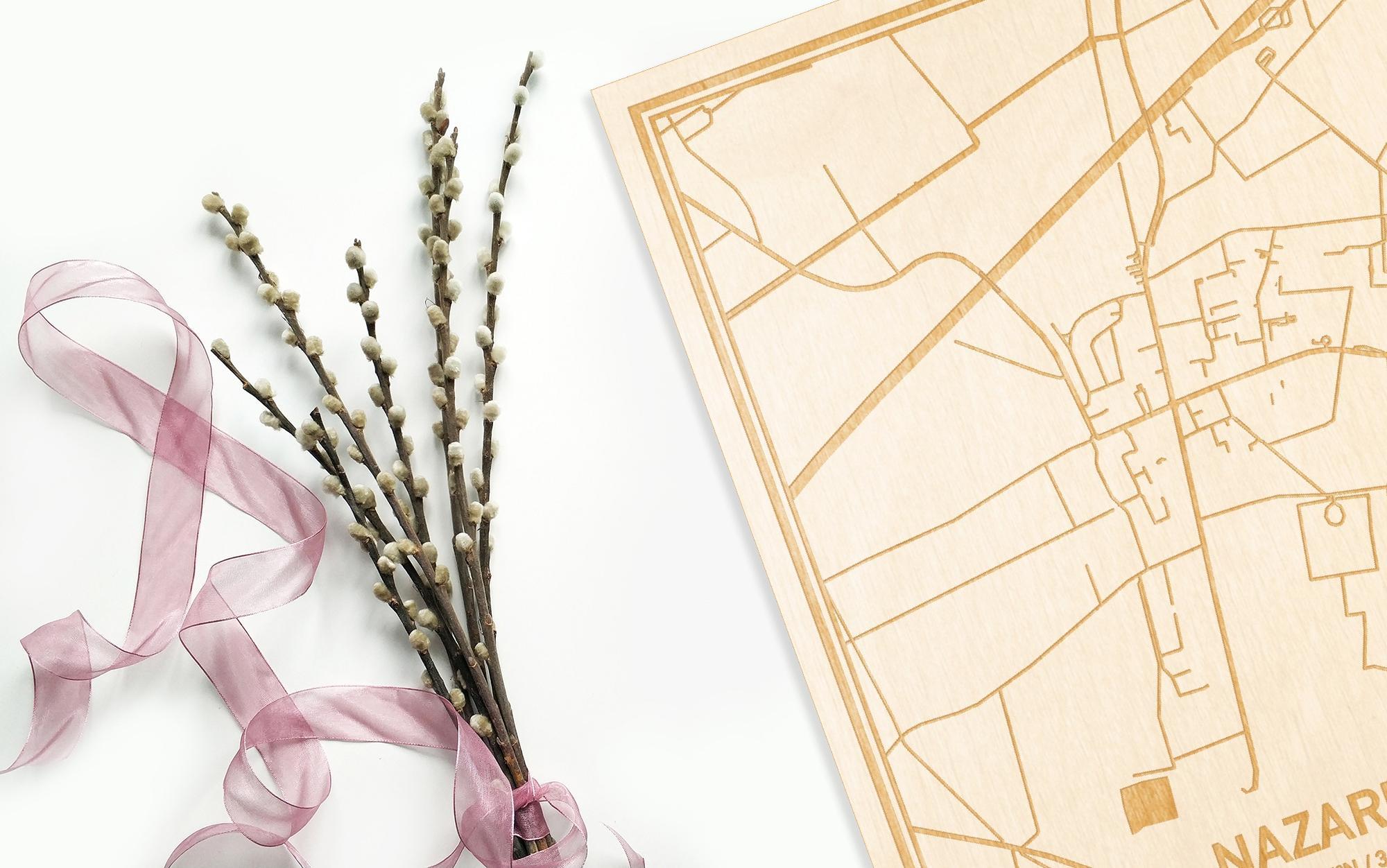 Hier ligt de houten plattegrond Nazareth naast een bloemetje als gepersonaliseerd cadeau voor haar.