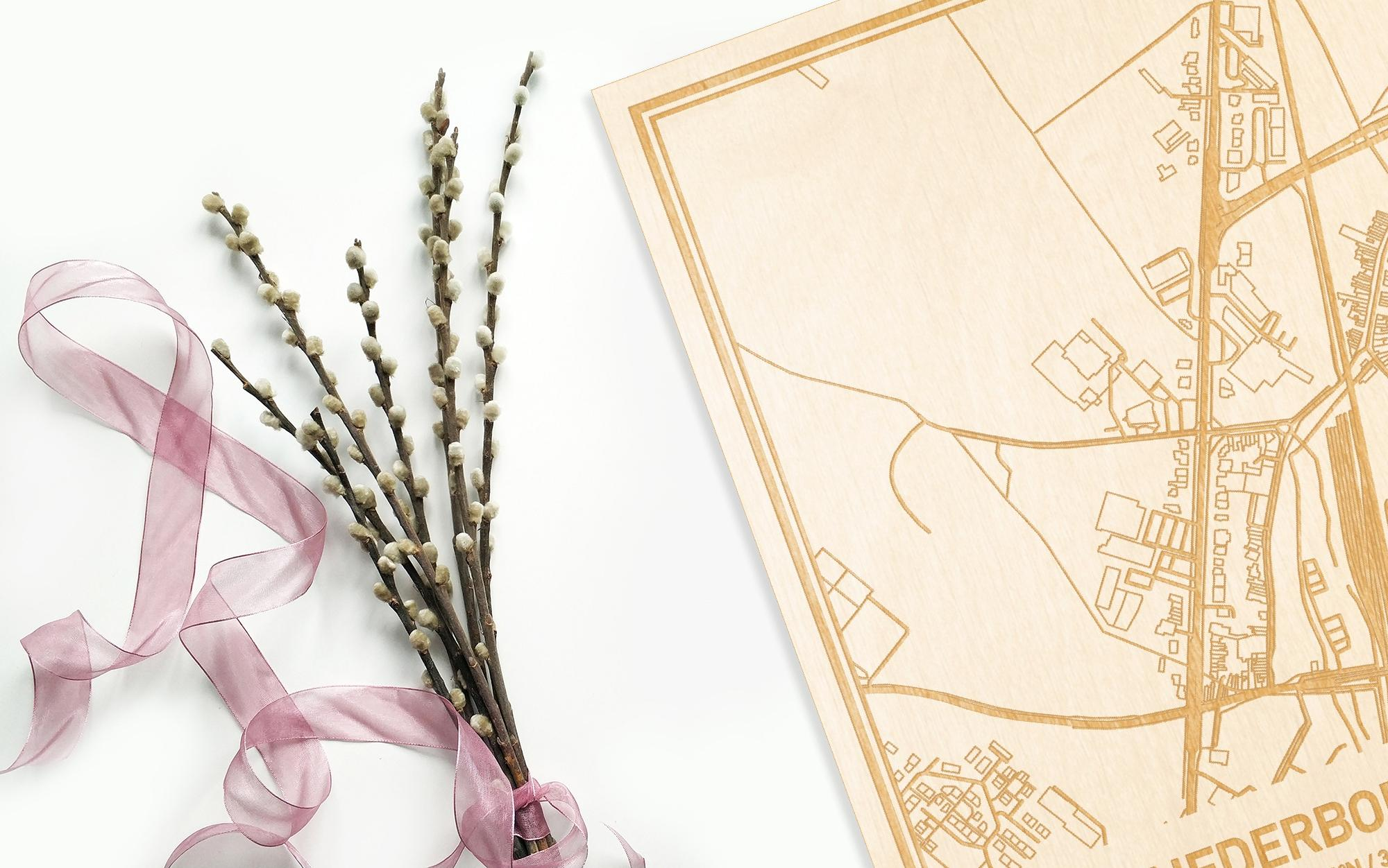Hier ligt de houten plattegrond Nederboelare naast een bloemetje als gepersonaliseerd cadeau voor haar.