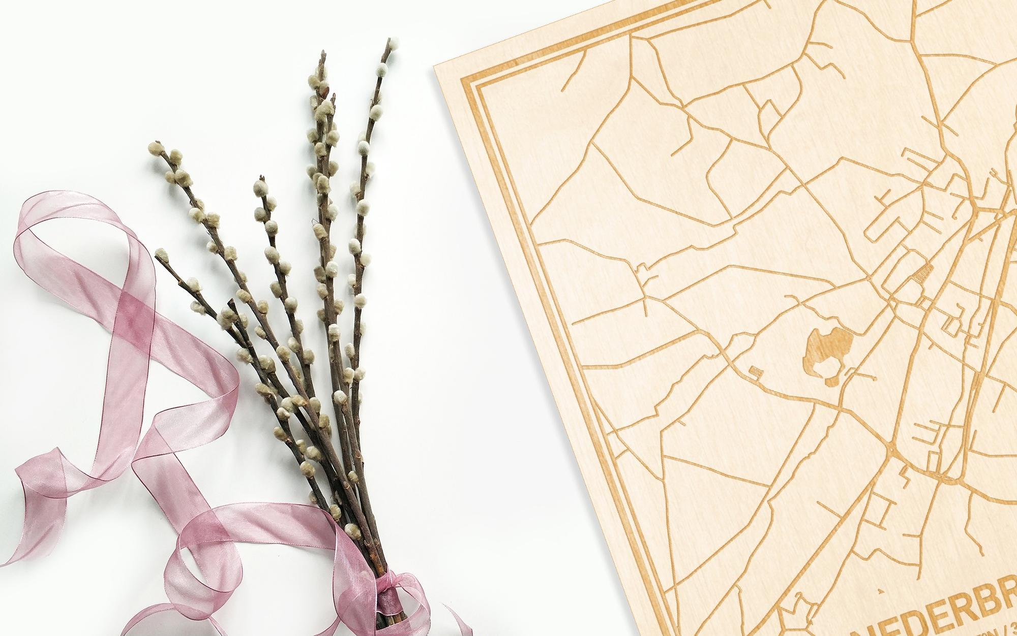 Hier ligt de houten plattegrond Nederbrakel naast een bloemetje als gepersonaliseerd cadeau voor haar.