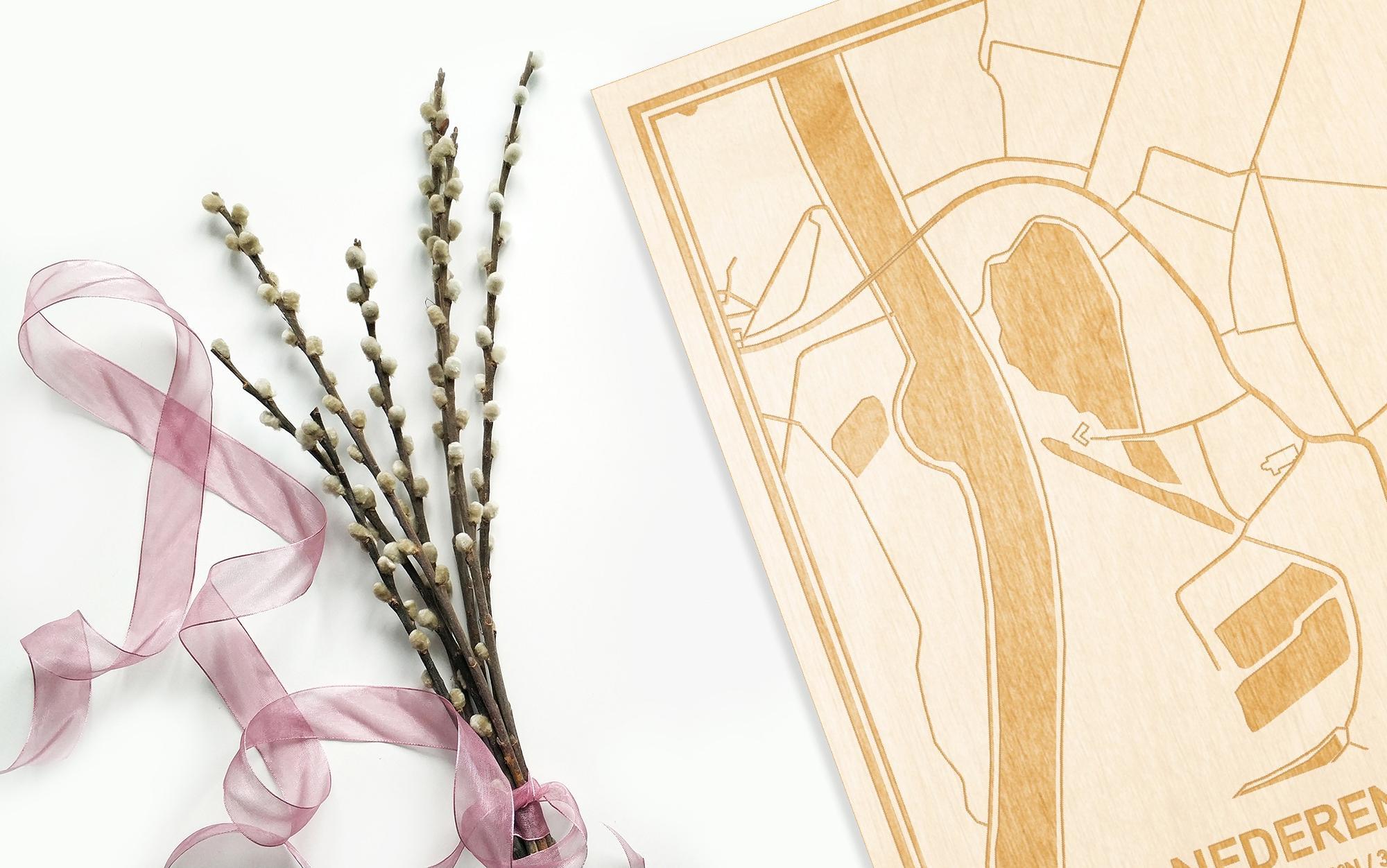Hier ligt de houten plattegrond Nederename naast een bloemetje als gepersonaliseerd cadeau voor haar.