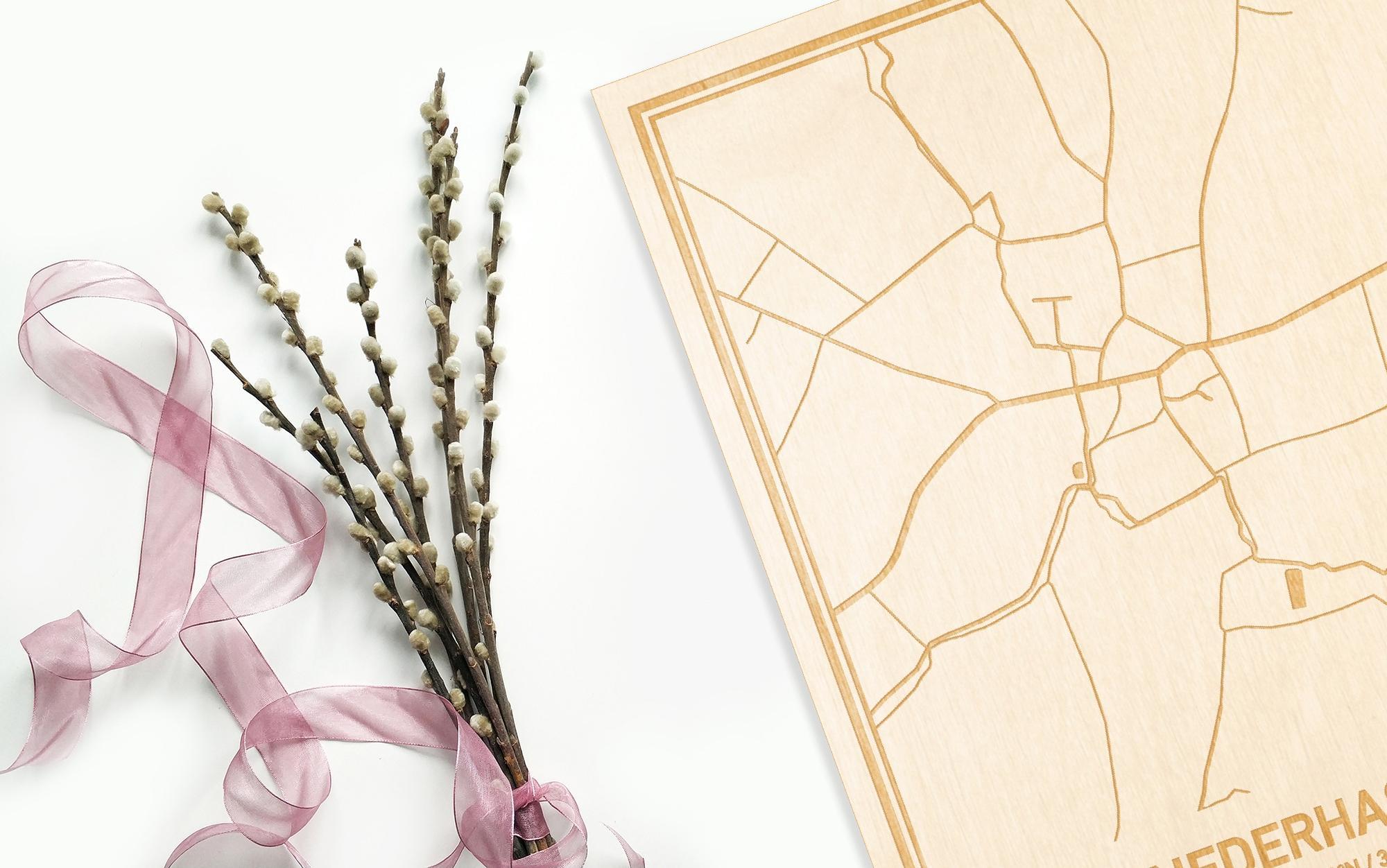 Hier ligt de houten plattegrond Nederhasselt naast een bloemetje als gepersonaliseerd cadeau voor haar.
