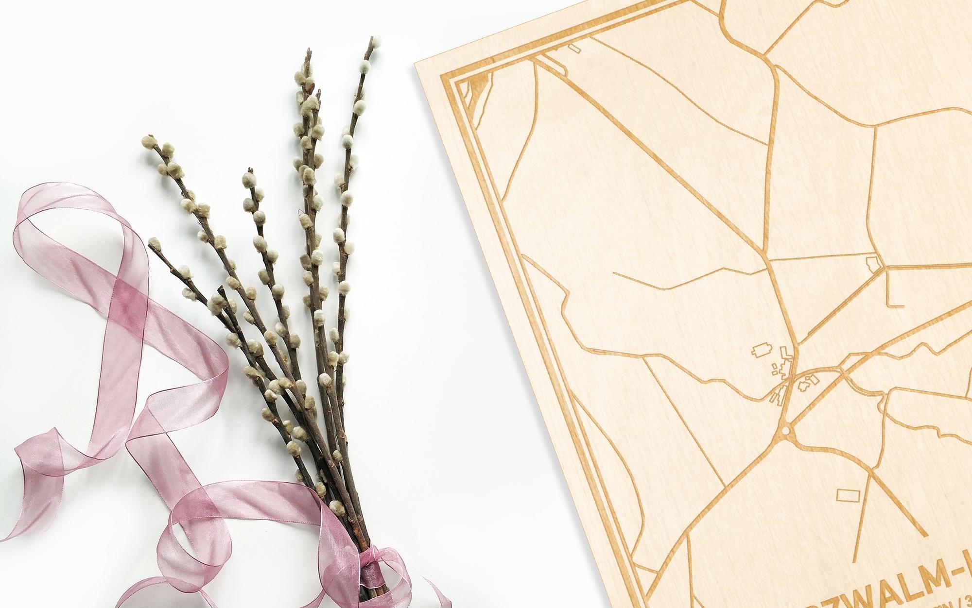Hier ligt de houten plattegrond Nederzwalm-Hermelgem naast een bloemetje als gepersonaliseerd cadeau voor haar.