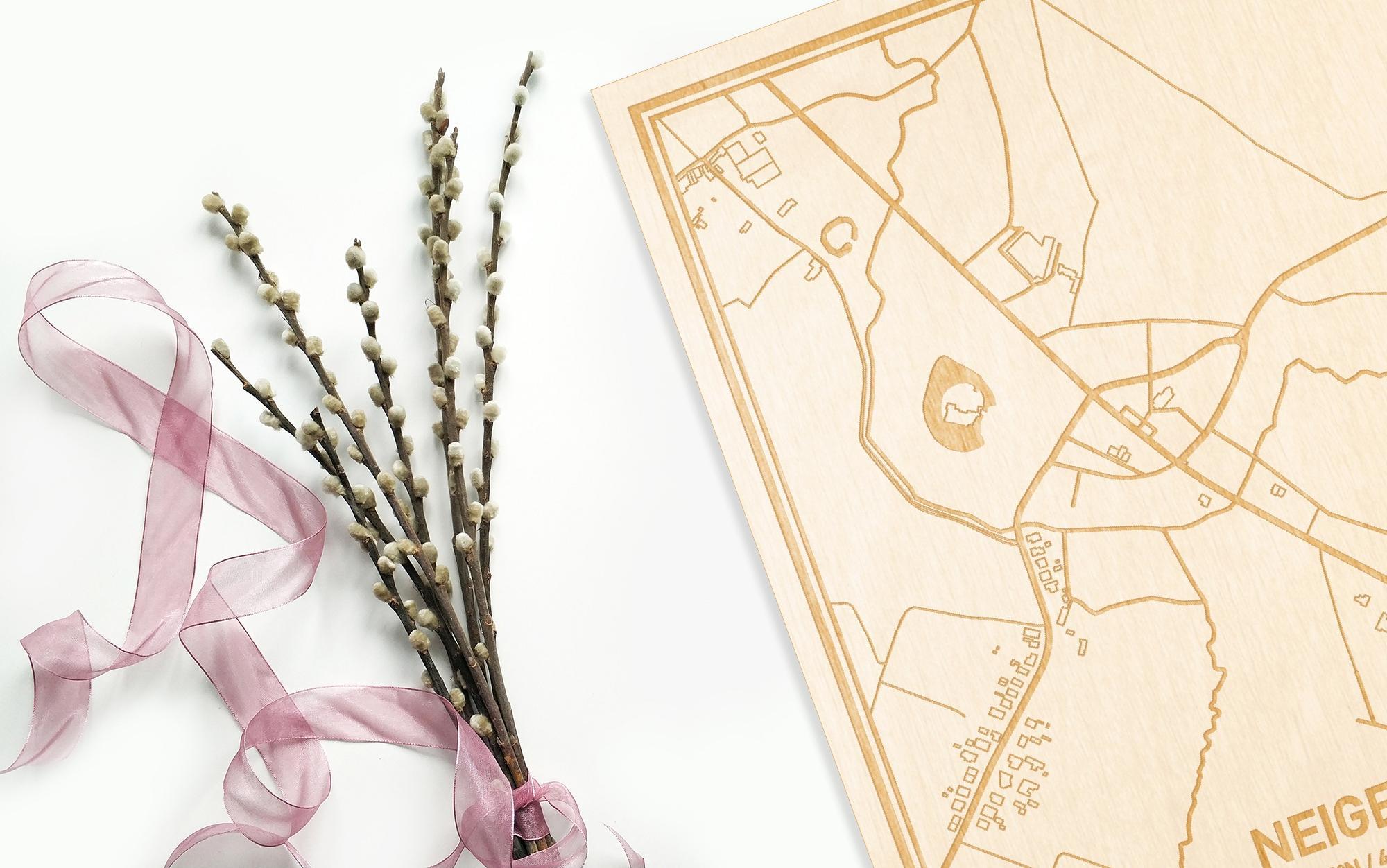 Hier ligt de houten plattegrond Neigem naast een bloemetje als gepersonaliseerd cadeau voor haar.