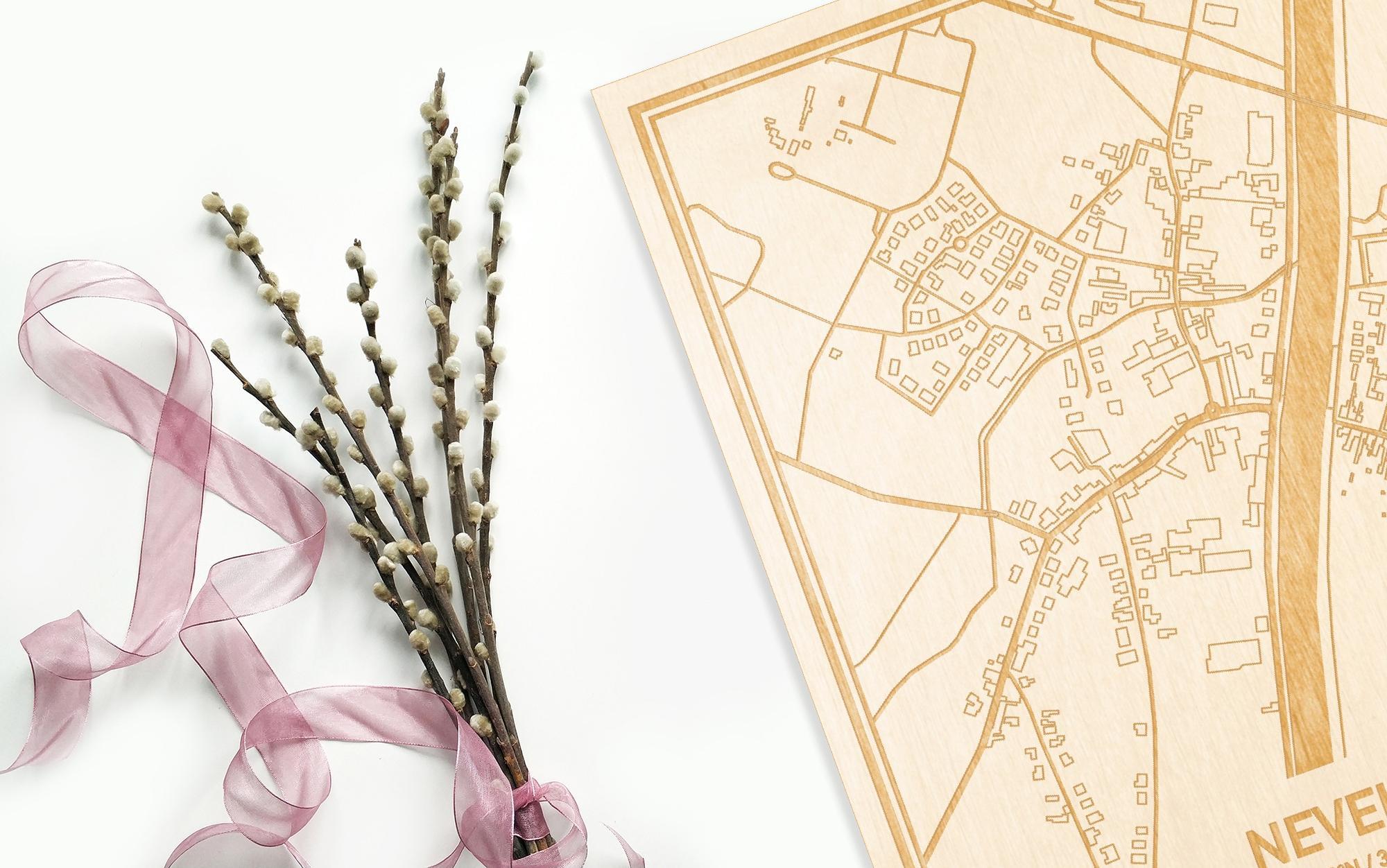 Hier ligt de houten plattegrond Nevele naast een bloemetje als gepersonaliseerd cadeau voor haar.