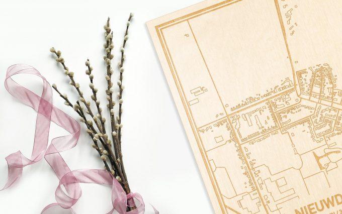 Hier ligt de houten plattegrond Nieuwdorp naast een bloemetje als gepersonaliseerd cadeau voor haar.