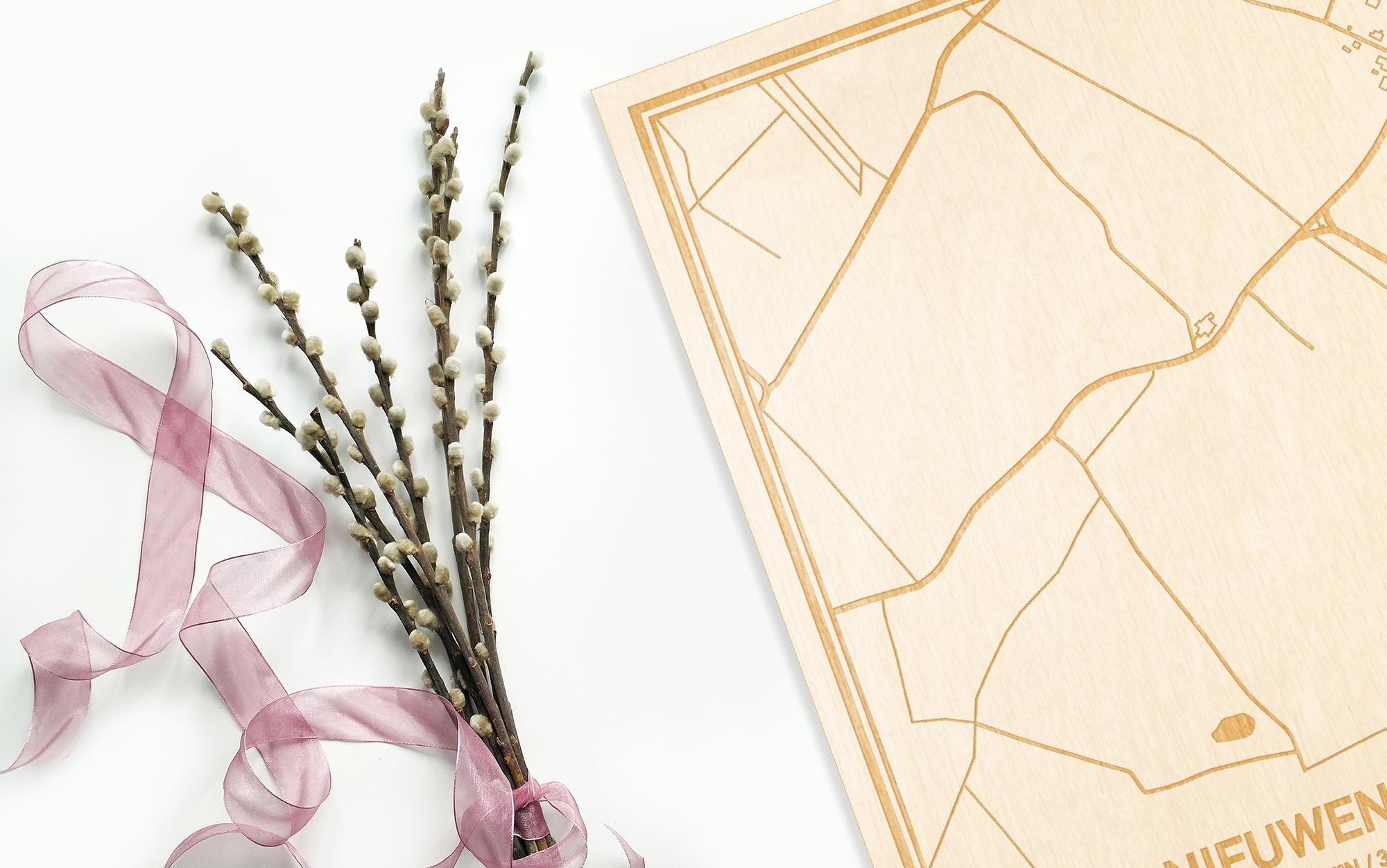 Hier ligt de houten plattegrond Nieuwenhove naast een bloemetje als gepersonaliseerd cadeau voor haar.