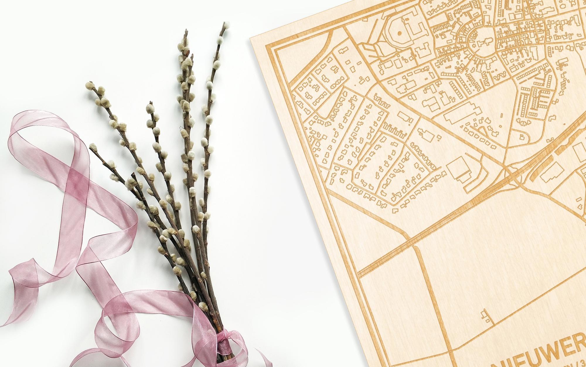 Hier ligt de houten plattegrond Nieuwerkerk naast een bloemetje als gepersonaliseerd cadeau voor haar.