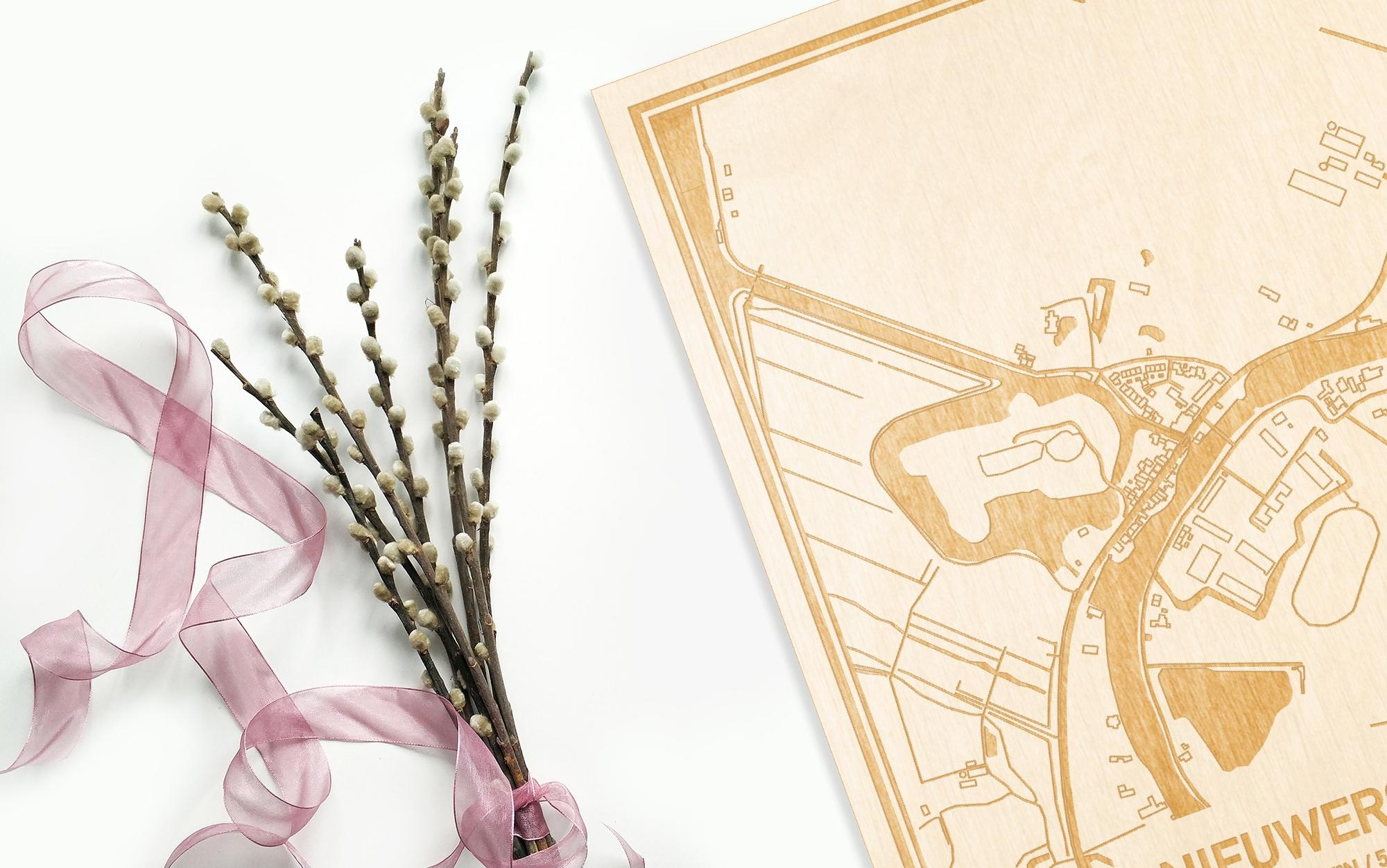 Hier ligt de houten plattegrond Nieuwersluis naast een bloemetje als gepersonaliseerd cadeau voor haar.