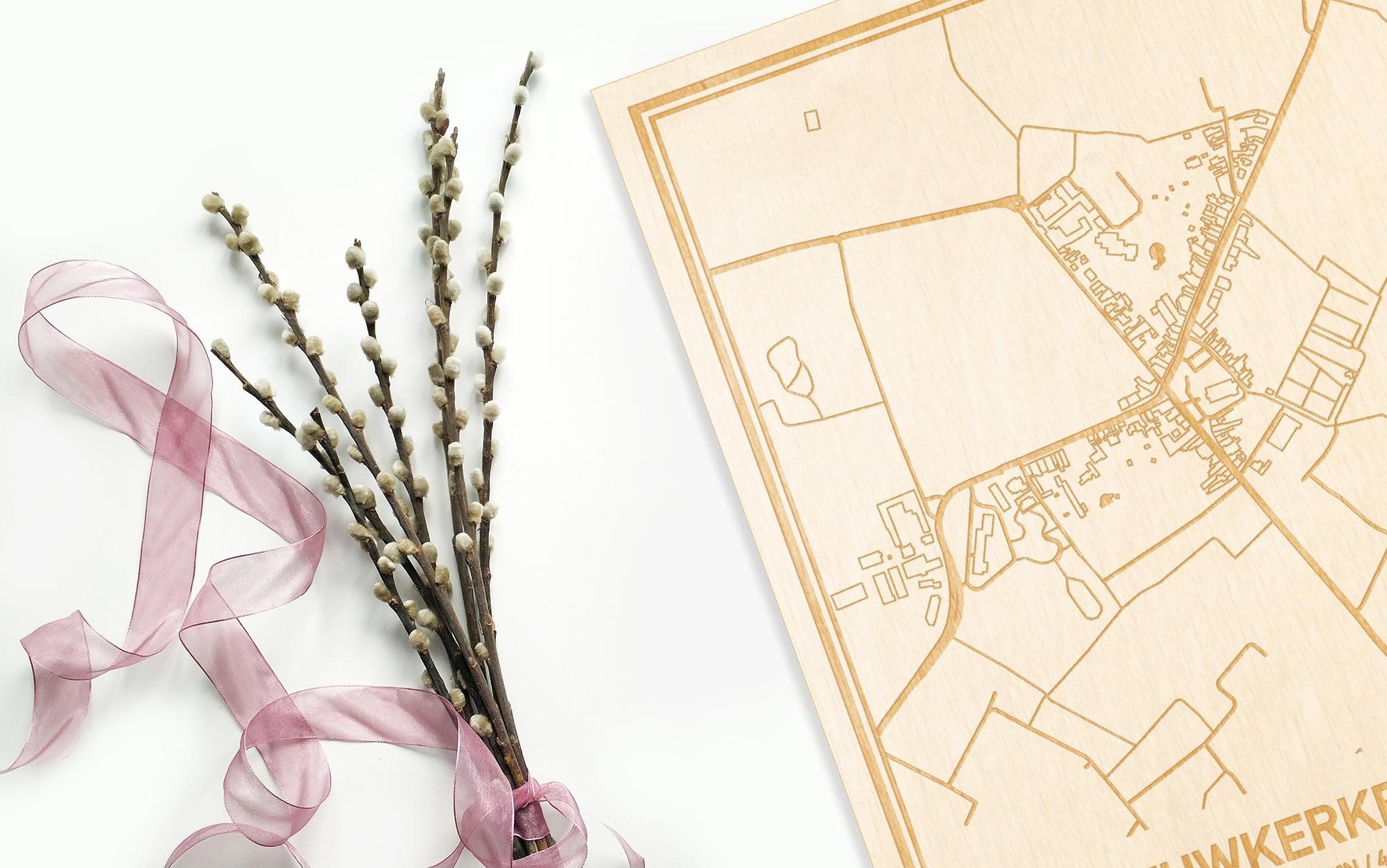 Hier ligt de houten plattegrond Nieuwkerken-Waas naast een bloemetje als gepersonaliseerd cadeau voor haar.