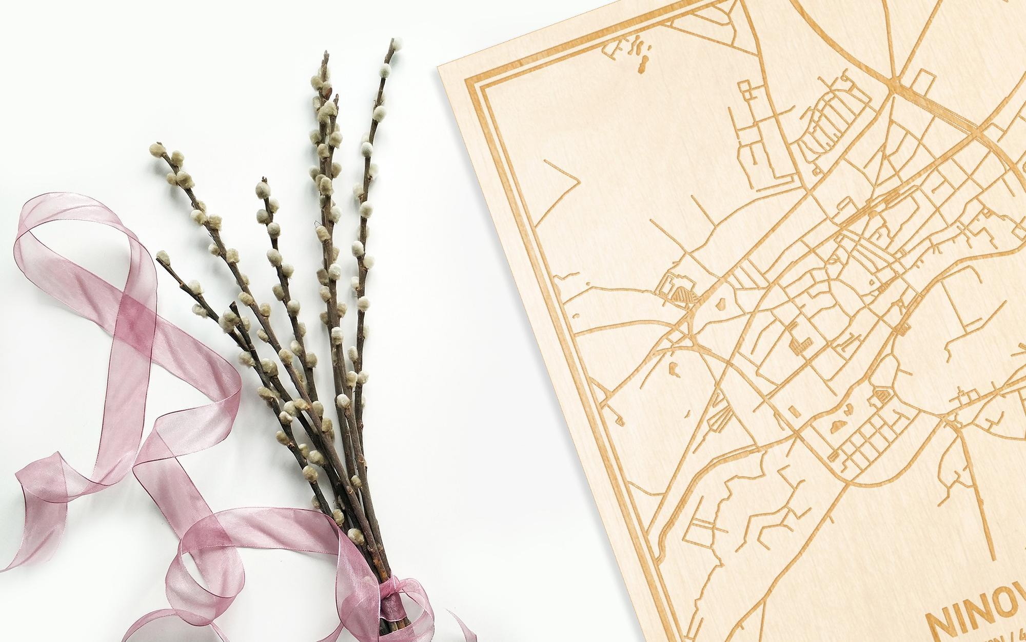 Hier ligt de houten plattegrond Ninove naast een bloemetje als gepersonaliseerd cadeau voor haar.
