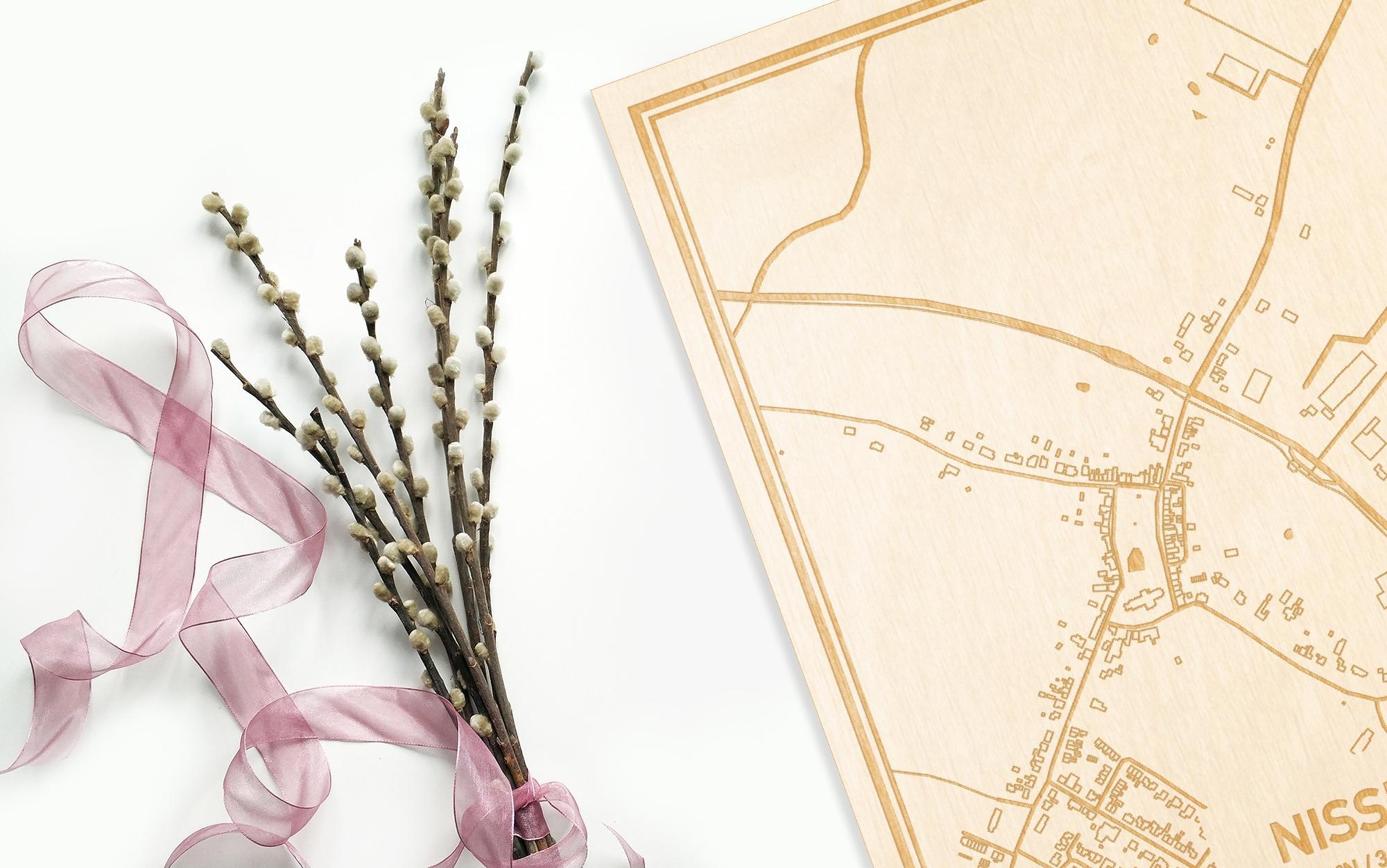 Hier ligt de houten plattegrond Nisse naast een bloemetje als gepersonaliseerd cadeau voor haar.