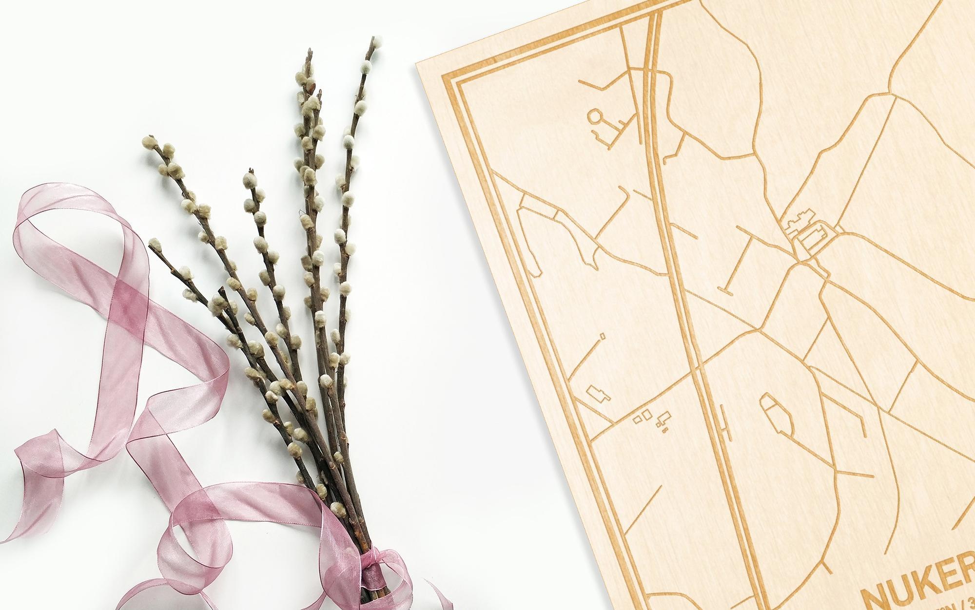 Hier ligt de houten plattegrond Nukerke naast een bloemetje als gepersonaliseerd cadeau voor haar.