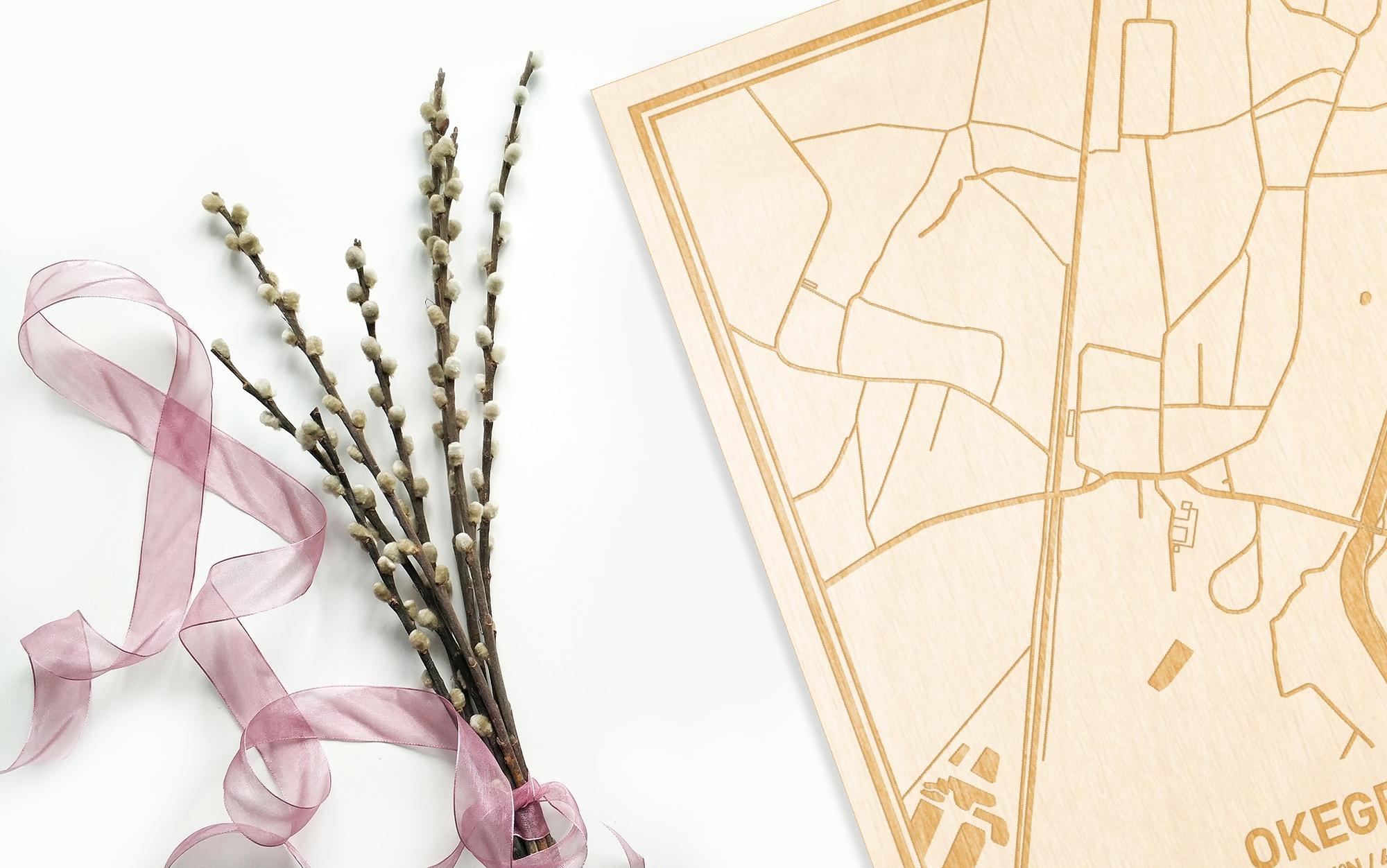 Hier ligt de houten plattegrond Okegem naast een bloemetje als gepersonaliseerd cadeau voor haar.