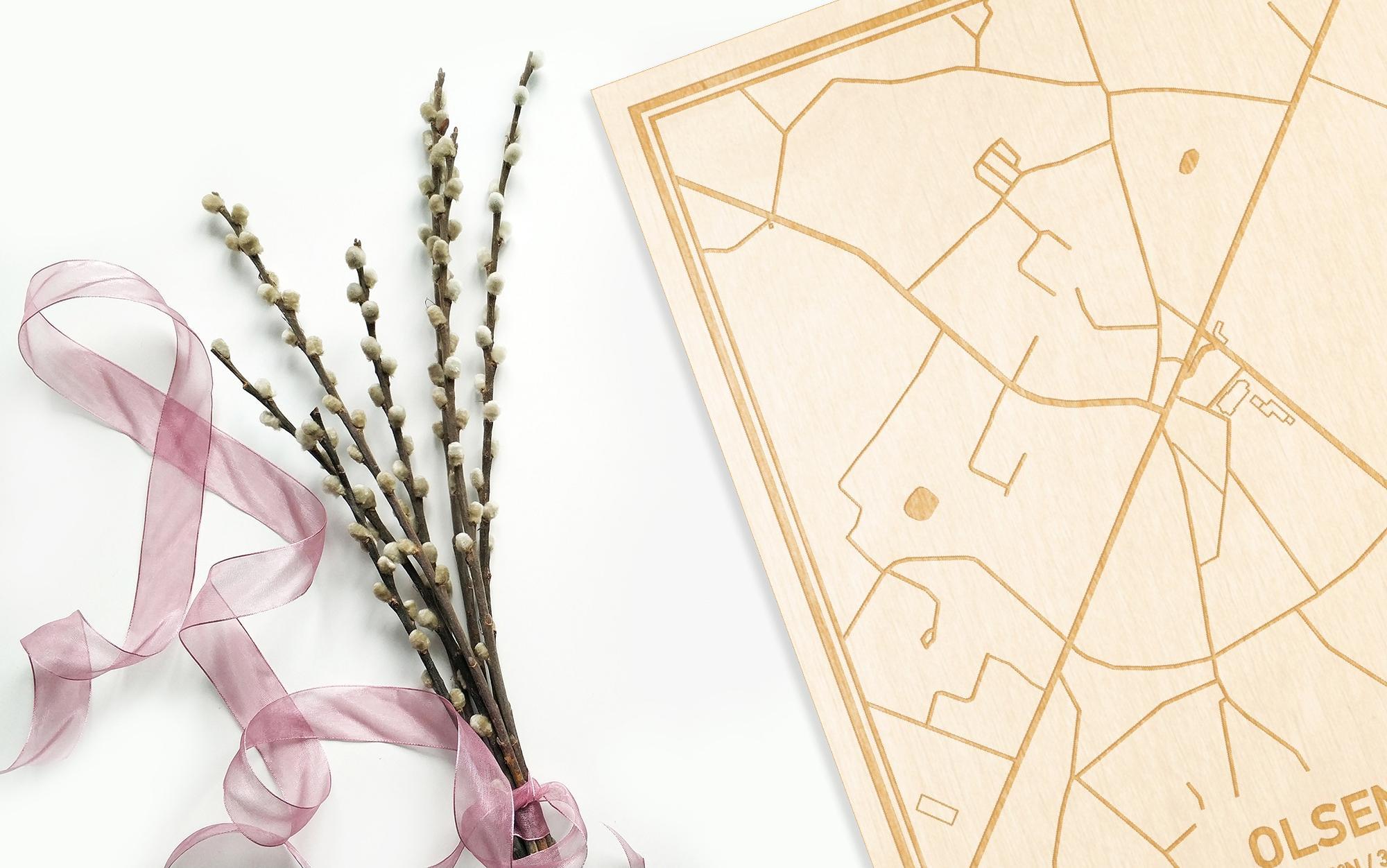 Hier ligt de houten plattegrond Olsene naast een bloemetje als gepersonaliseerd cadeau voor haar.