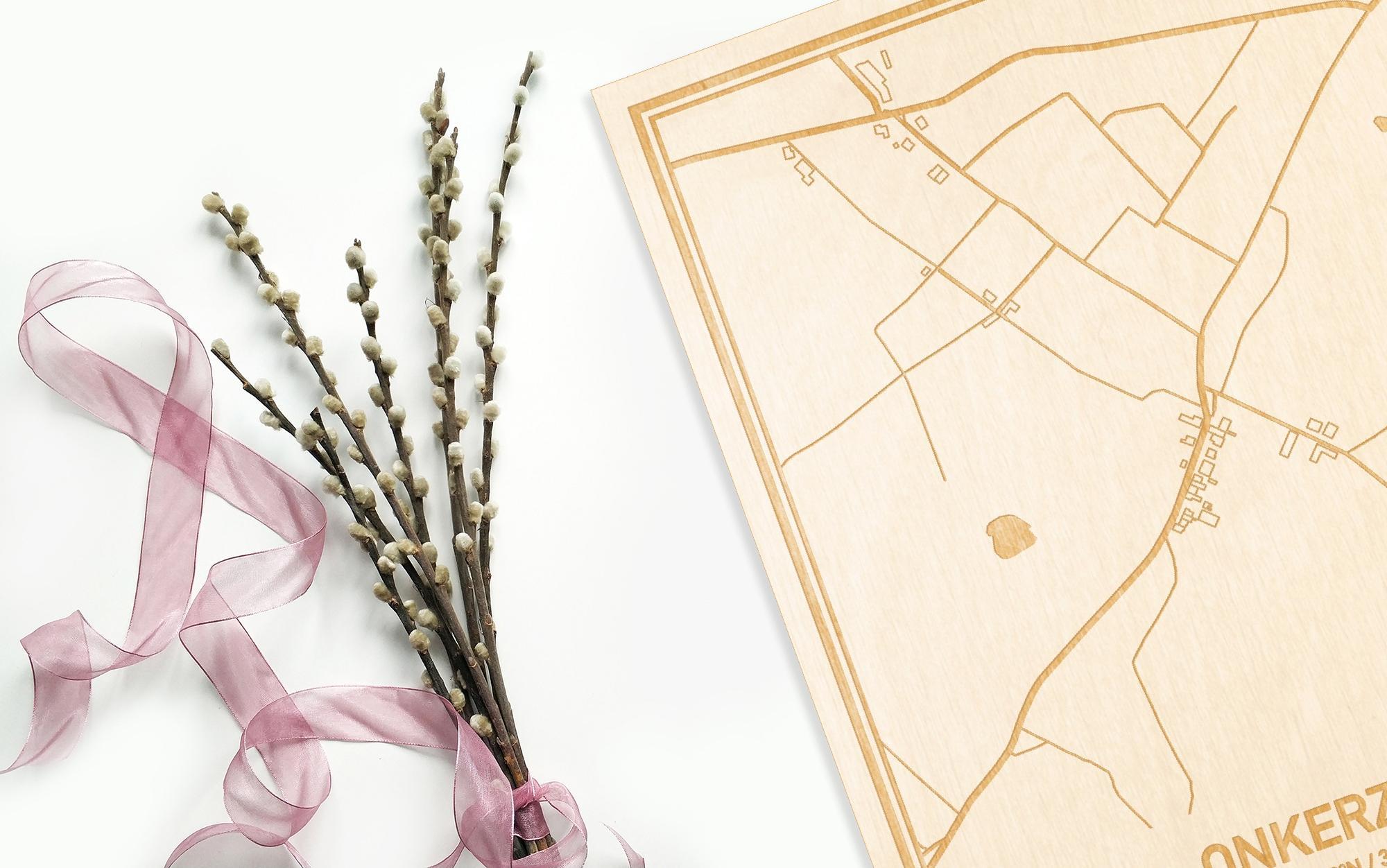 Hier ligt de houten plattegrond Onkerzele naast een bloemetje als gepersonaliseerd cadeau voor haar.