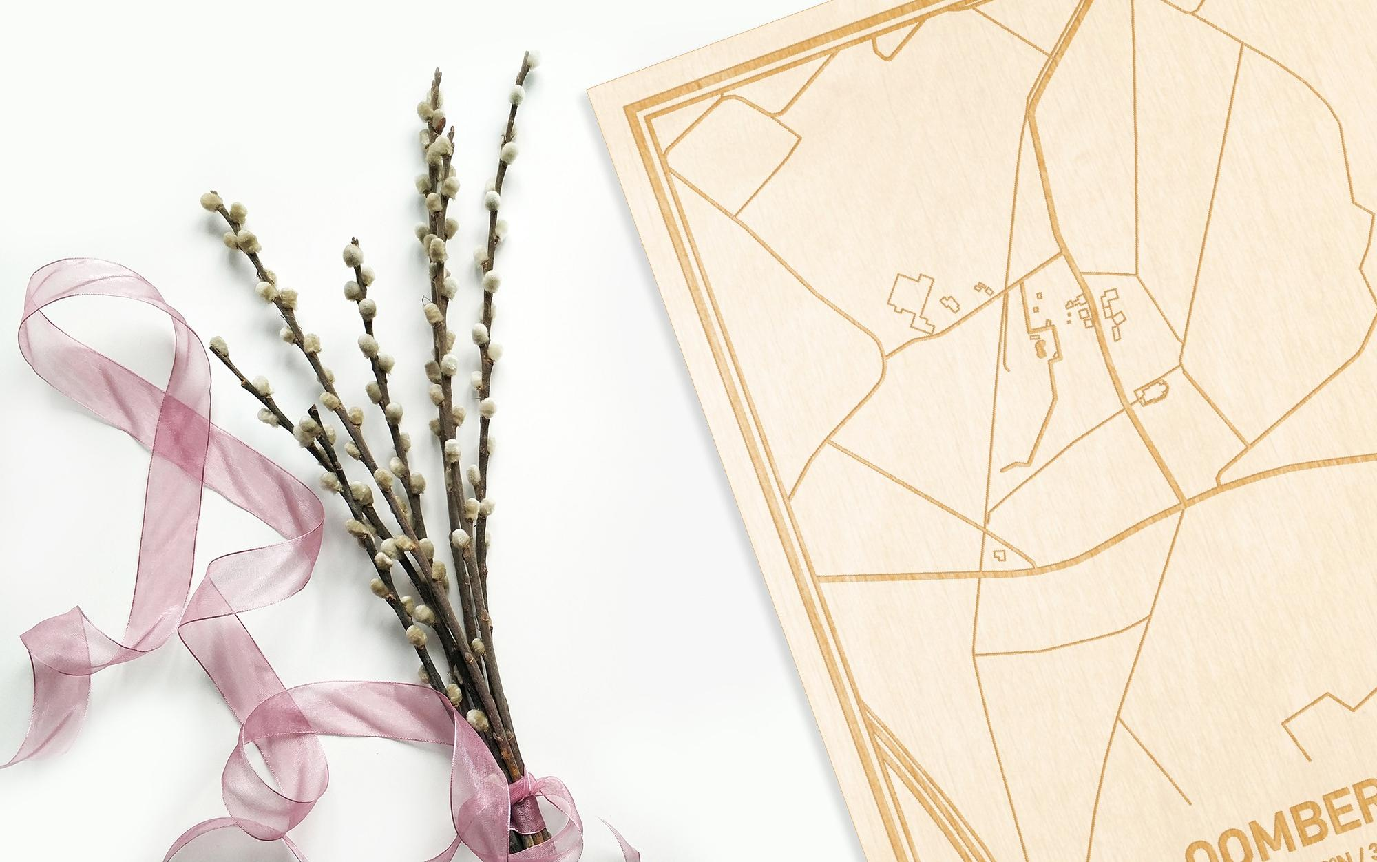 Hier ligt de houten plattegrond Oombergen naast een bloemetje als gepersonaliseerd cadeau voor haar.