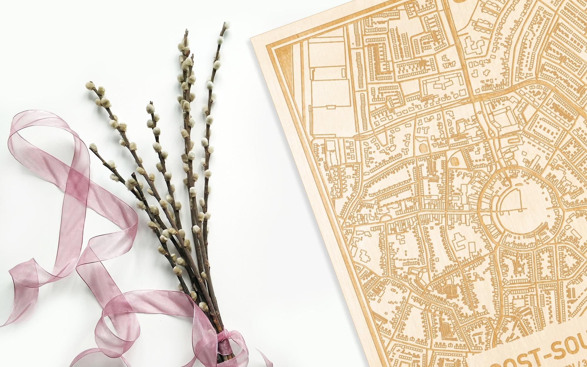 Hier ligt de houten plattegrond Oost-Souburg naast een bloemetje als gepersonaliseerd cadeau voor haar.