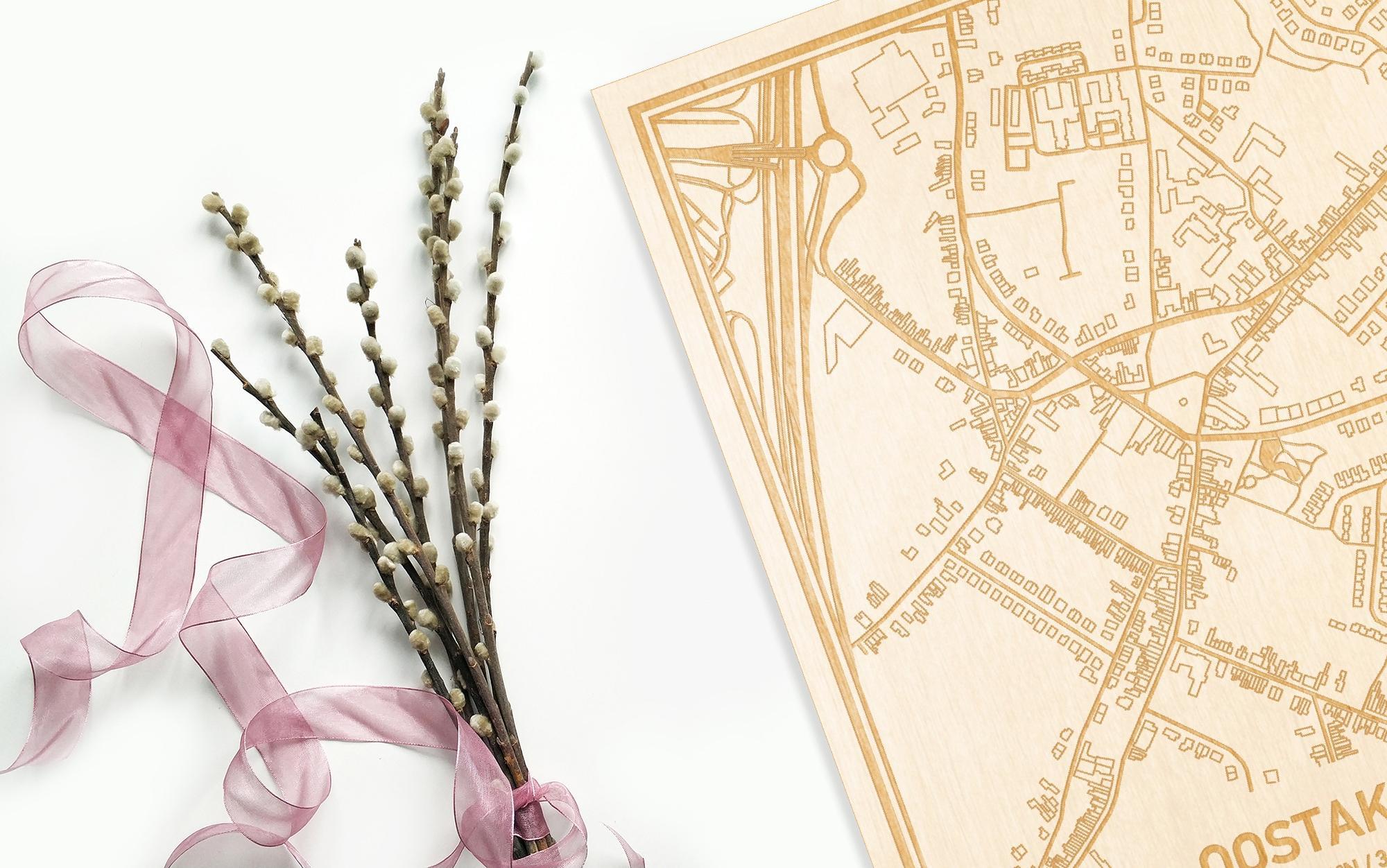 Hier ligt de houten plattegrond Oostakker naast een bloemetje als gepersonaliseerd cadeau voor haar.