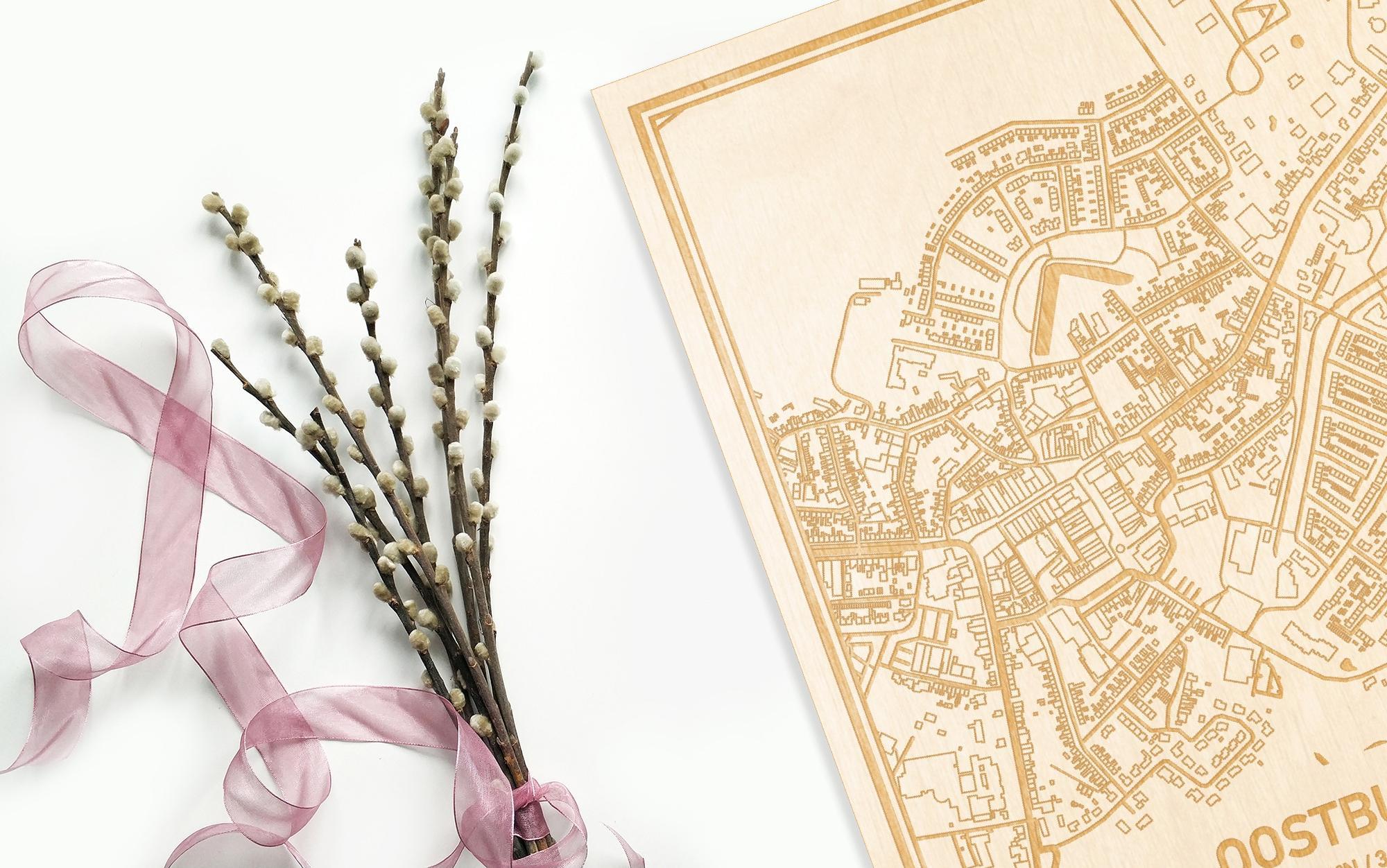 Hier ligt de houten plattegrond Oostburg naast een bloemetje als gepersonaliseerd cadeau voor haar.
