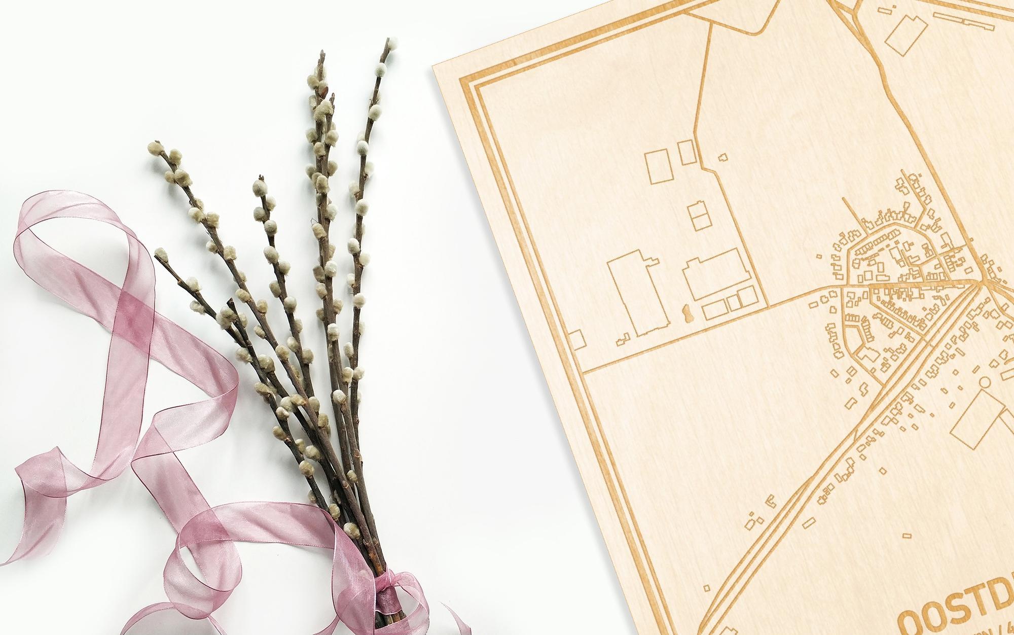 Hier ligt de houten plattegrond Oostdijk naast een bloemetje als gepersonaliseerd cadeau voor haar.
