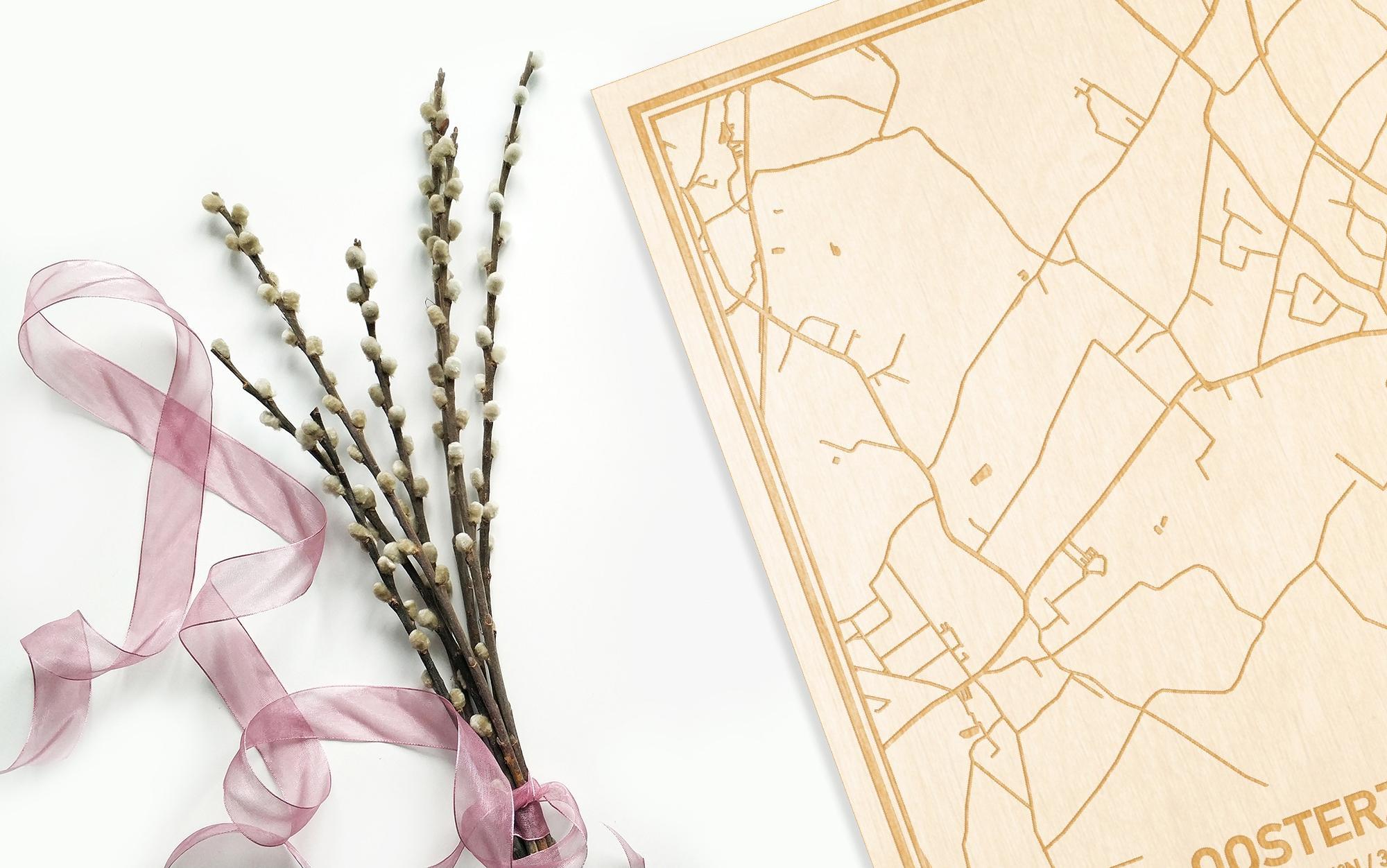 Hier ligt de houten plattegrond Oosterzele naast een bloemetje als gepersonaliseerd cadeau voor haar.