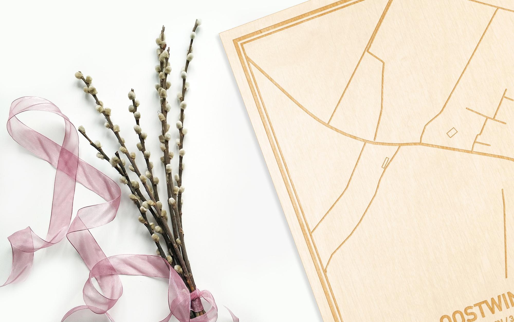 Hier ligt de houten plattegrond Oostwinkel naast een bloemetje als gepersonaliseerd cadeau voor haar.