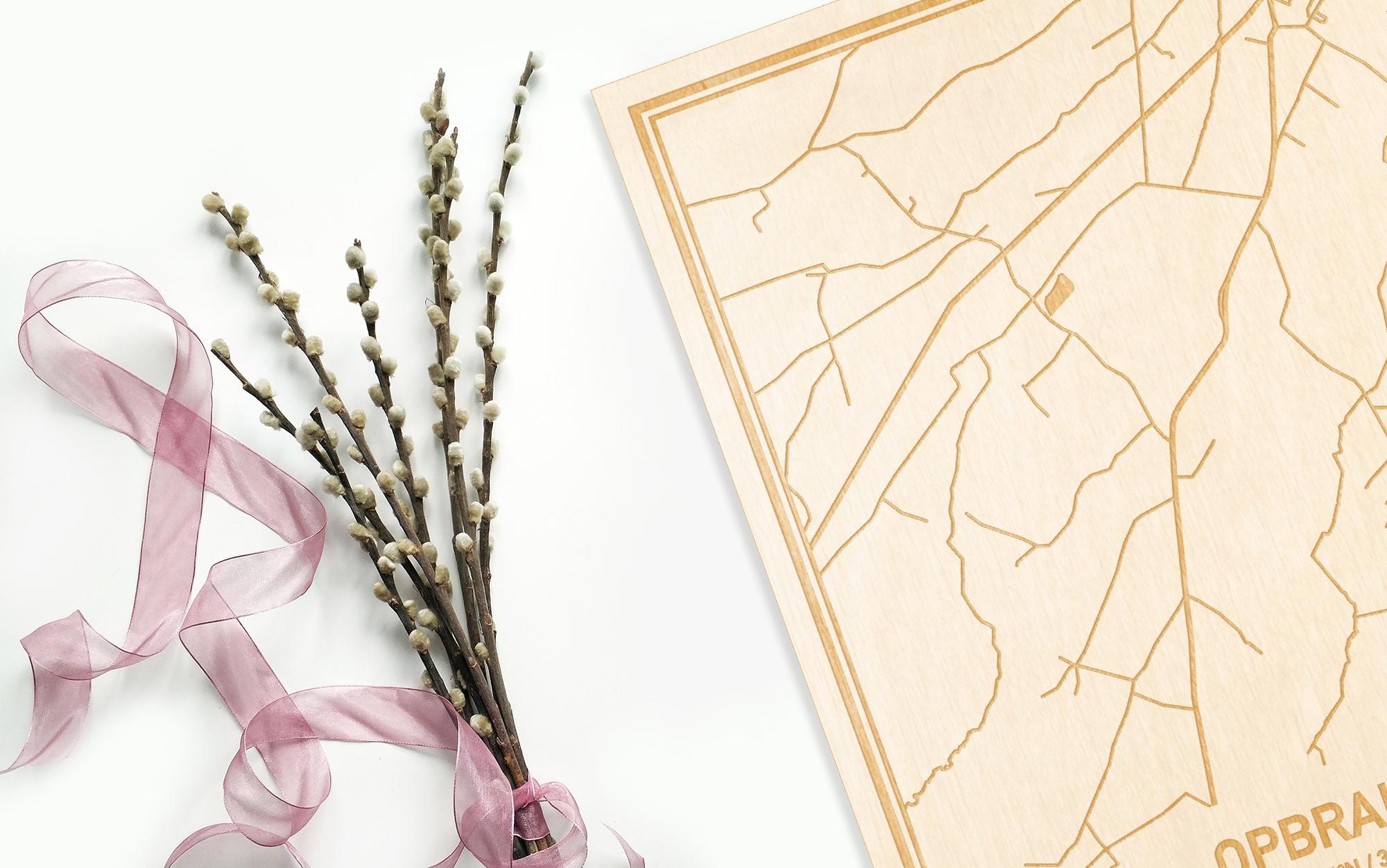 Hier ligt de houten plattegrond Opbrakel naast een bloemetje als gepersonaliseerd cadeau voor haar.