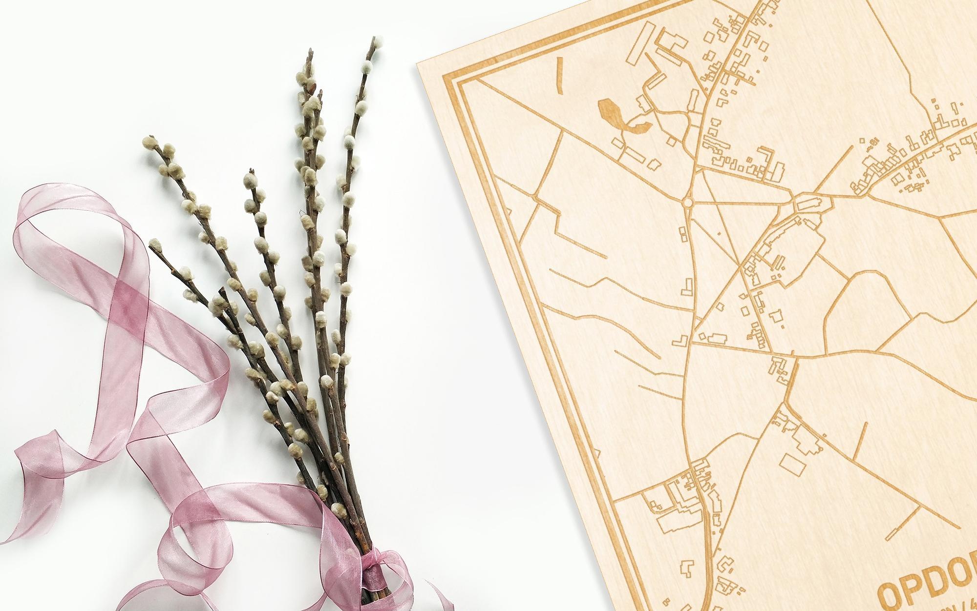 Hier ligt de houten plattegrond Opdorp naast een bloemetje als gepersonaliseerd cadeau voor haar.