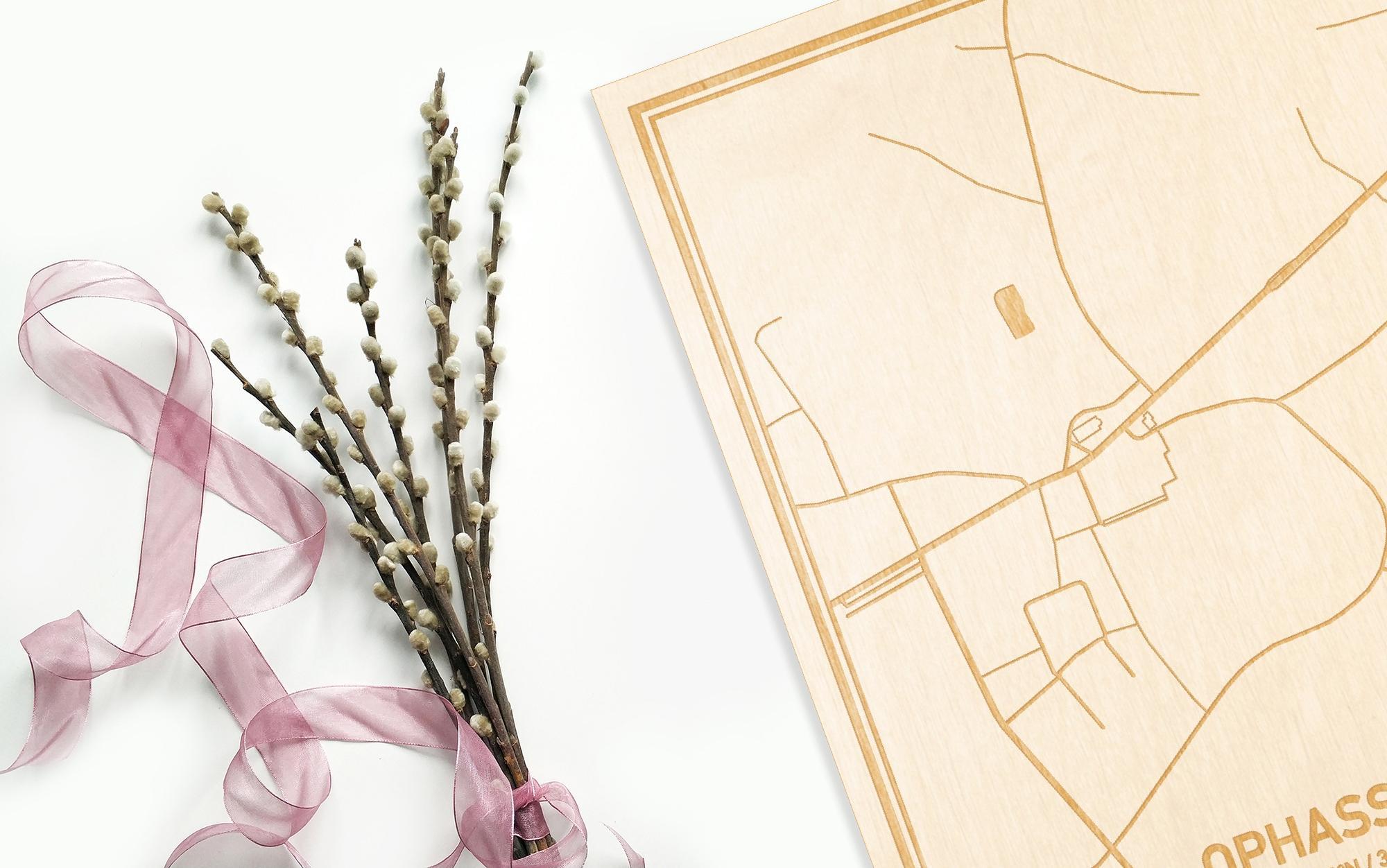 Hier ligt de houten plattegrond Ophasselt naast een bloemetje als gepersonaliseerd cadeau voor haar.