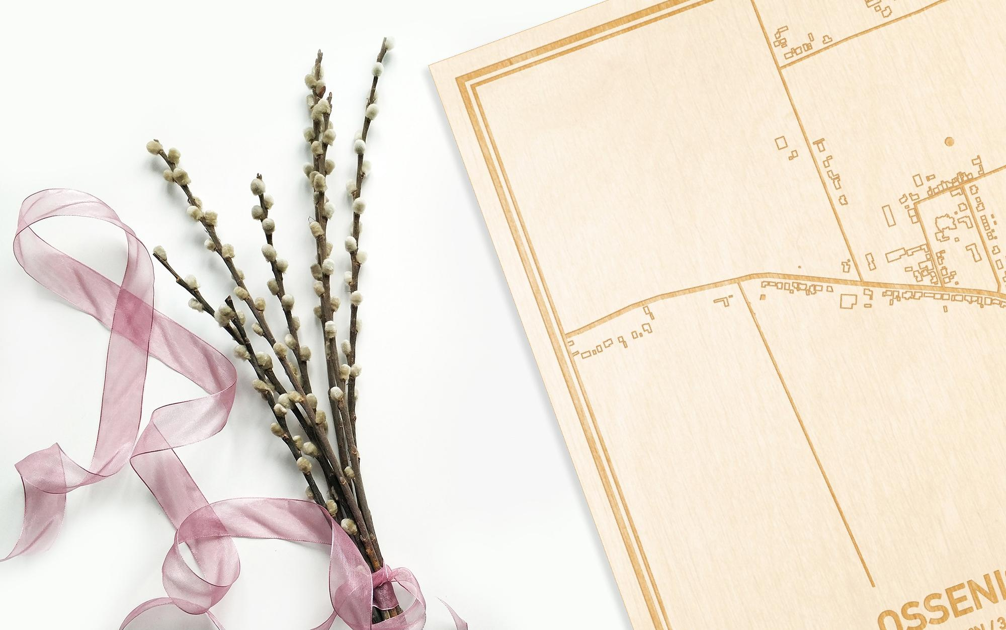 Hier ligt de houten plattegrond Ossenisse naast een bloemetje als gepersonaliseerd cadeau voor haar.