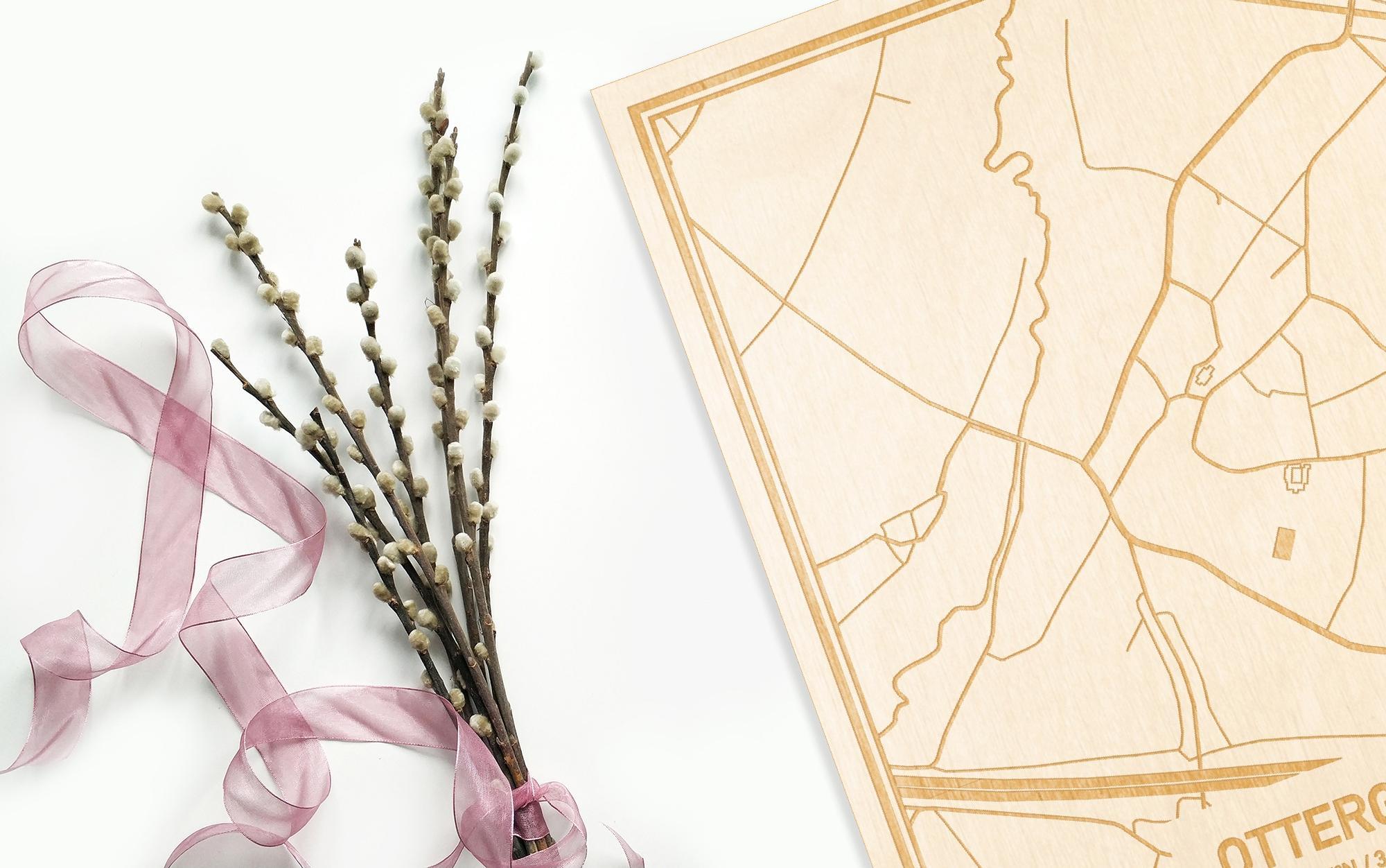 Hier ligt de houten plattegrond Ottergem naast een bloemetje als gepersonaliseerd cadeau voor haar.