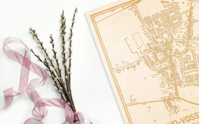 Hier ligt de houten plattegrond Oud-Vossemeer naast een bloemetje als gepersonaliseerd cadeau voor haar.