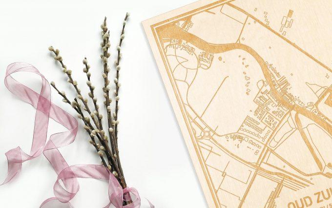 Hier ligt de houten plattegrond Oud Zuilen naast een bloemetje als gepersonaliseerd cadeau voor haar.