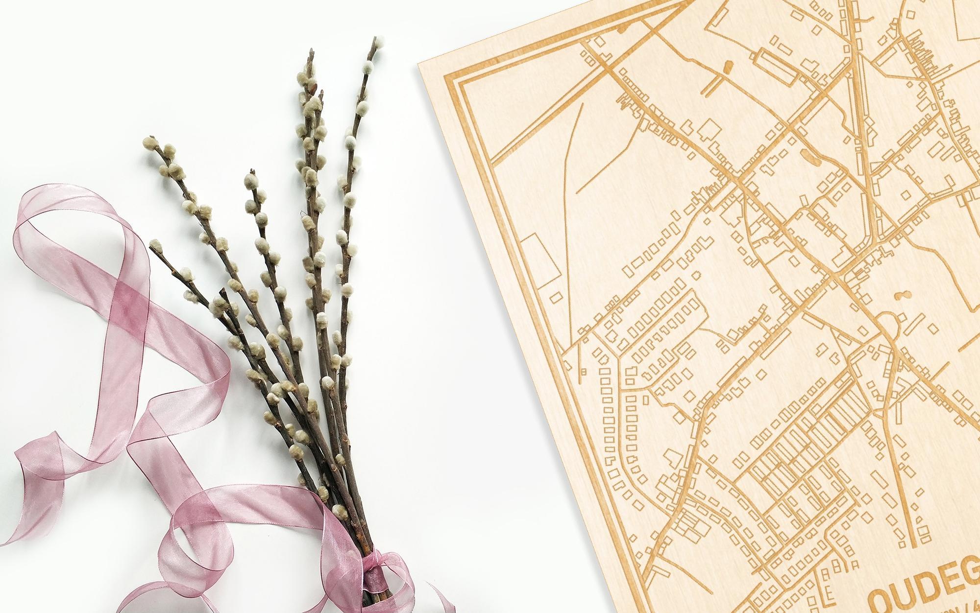 Hier ligt de houten plattegrond Oudegem naast een bloemetje als gepersonaliseerd cadeau voor haar.