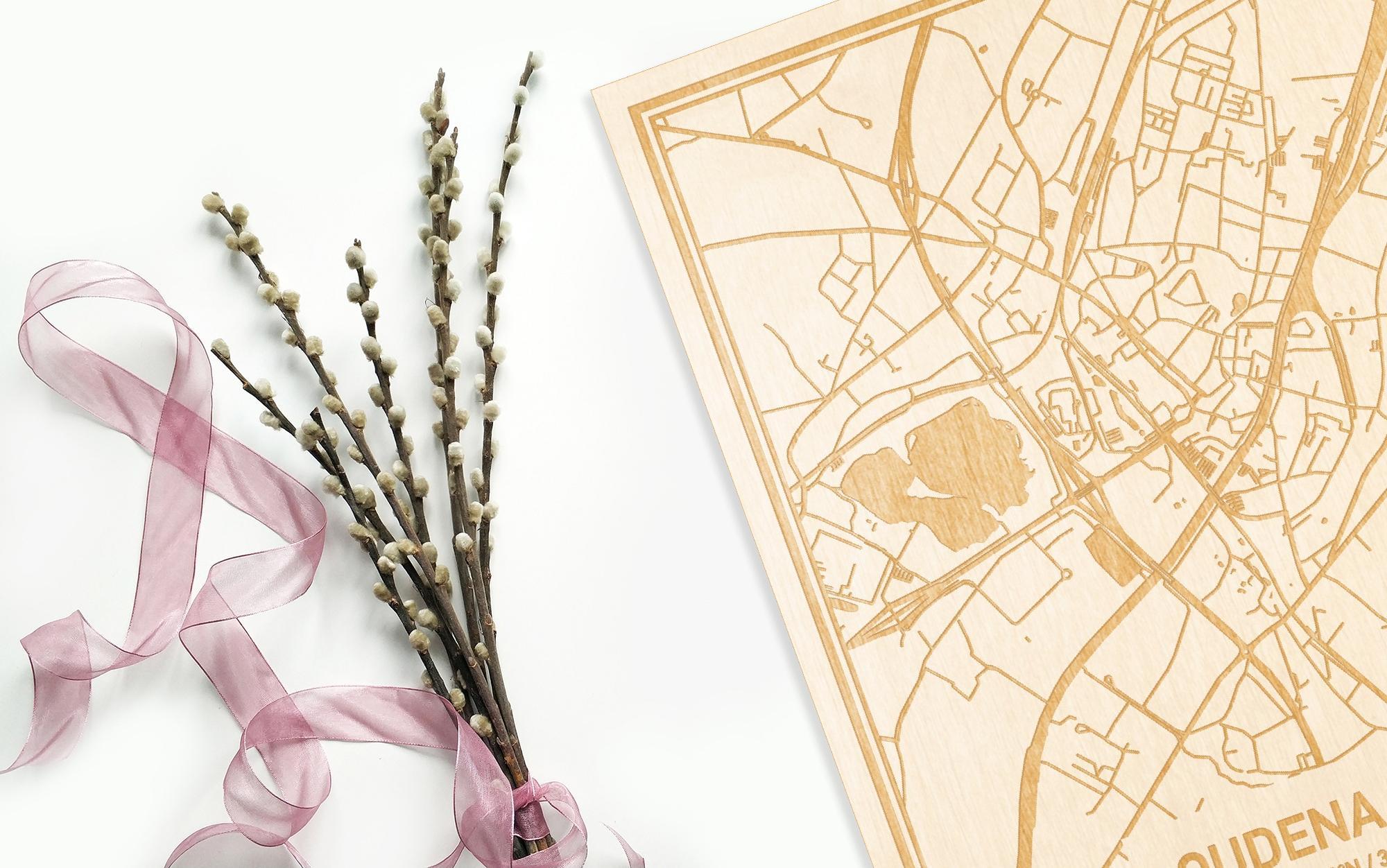Hier ligt de houten plattegrond Oudenaarde naast een bloemetje als gepersonaliseerd cadeau voor haar.